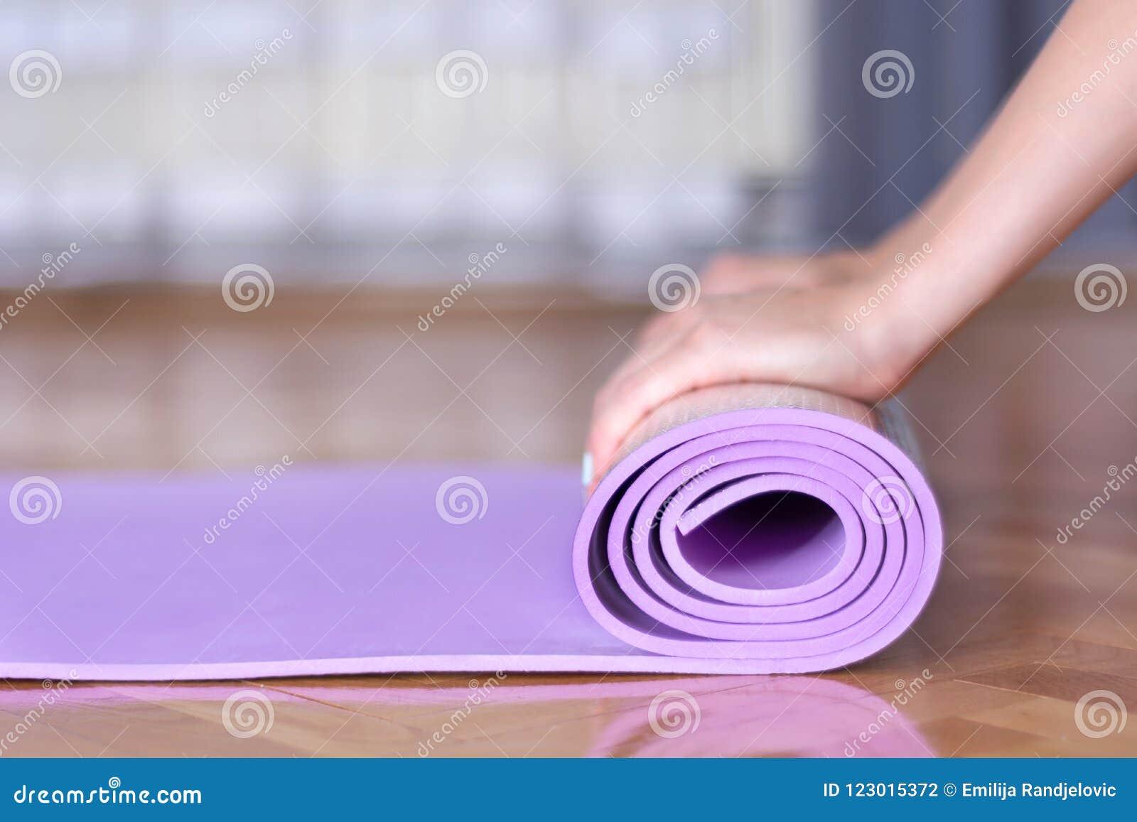 Las manos femeninas jovenes ruedan la estera púrpura de la yoga o de la aptitud en piso de entarimado