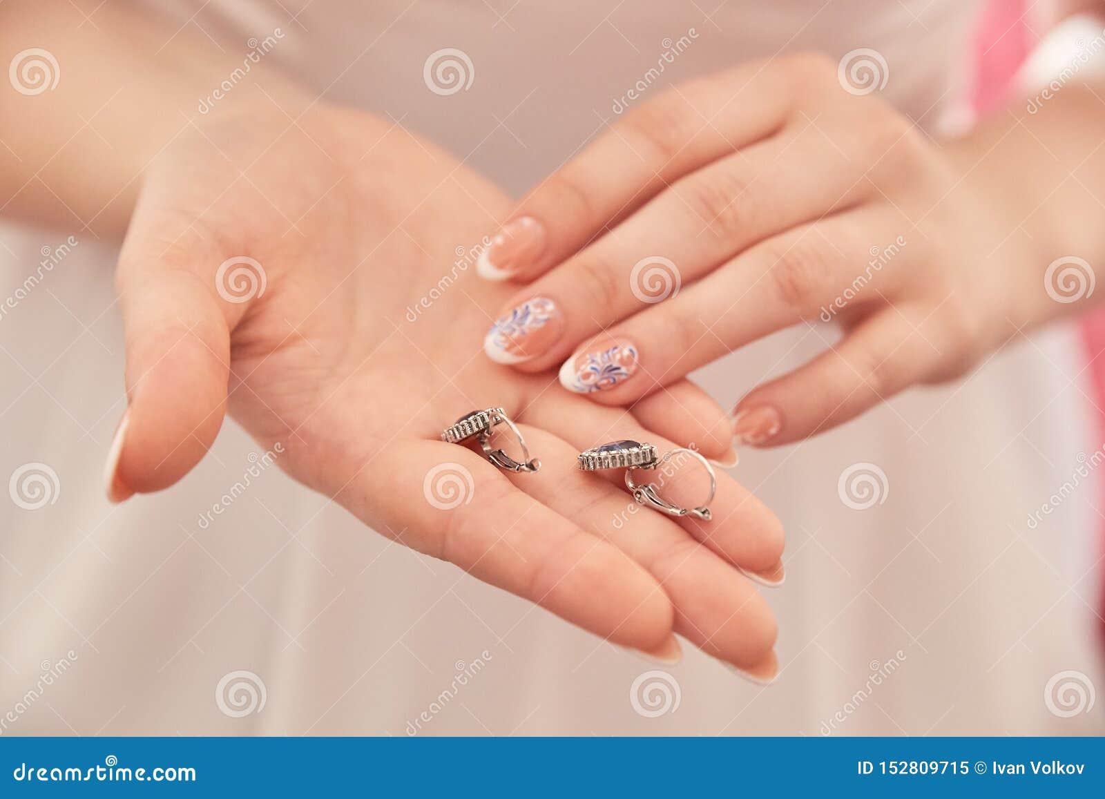 Las manos hermosas de las mujeres llevan a cabo los anillos de bodas
