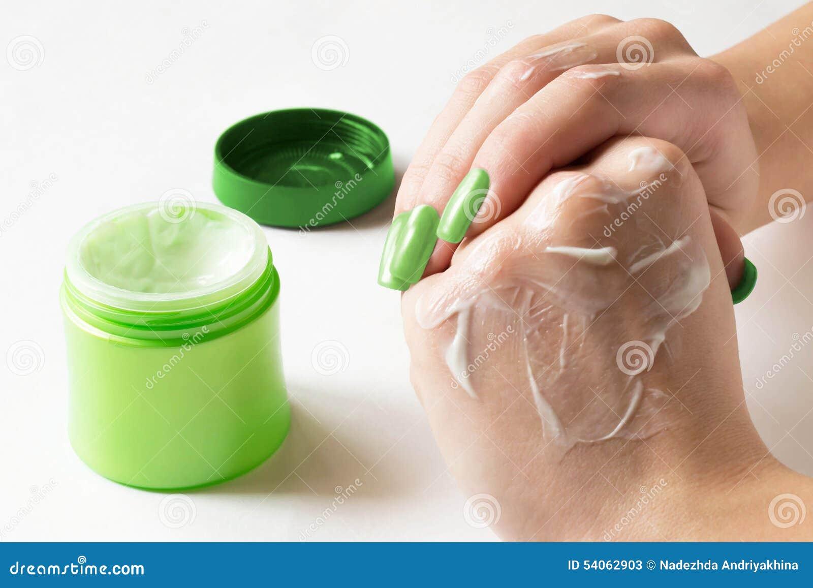 Las manos manchan la crema en la piel