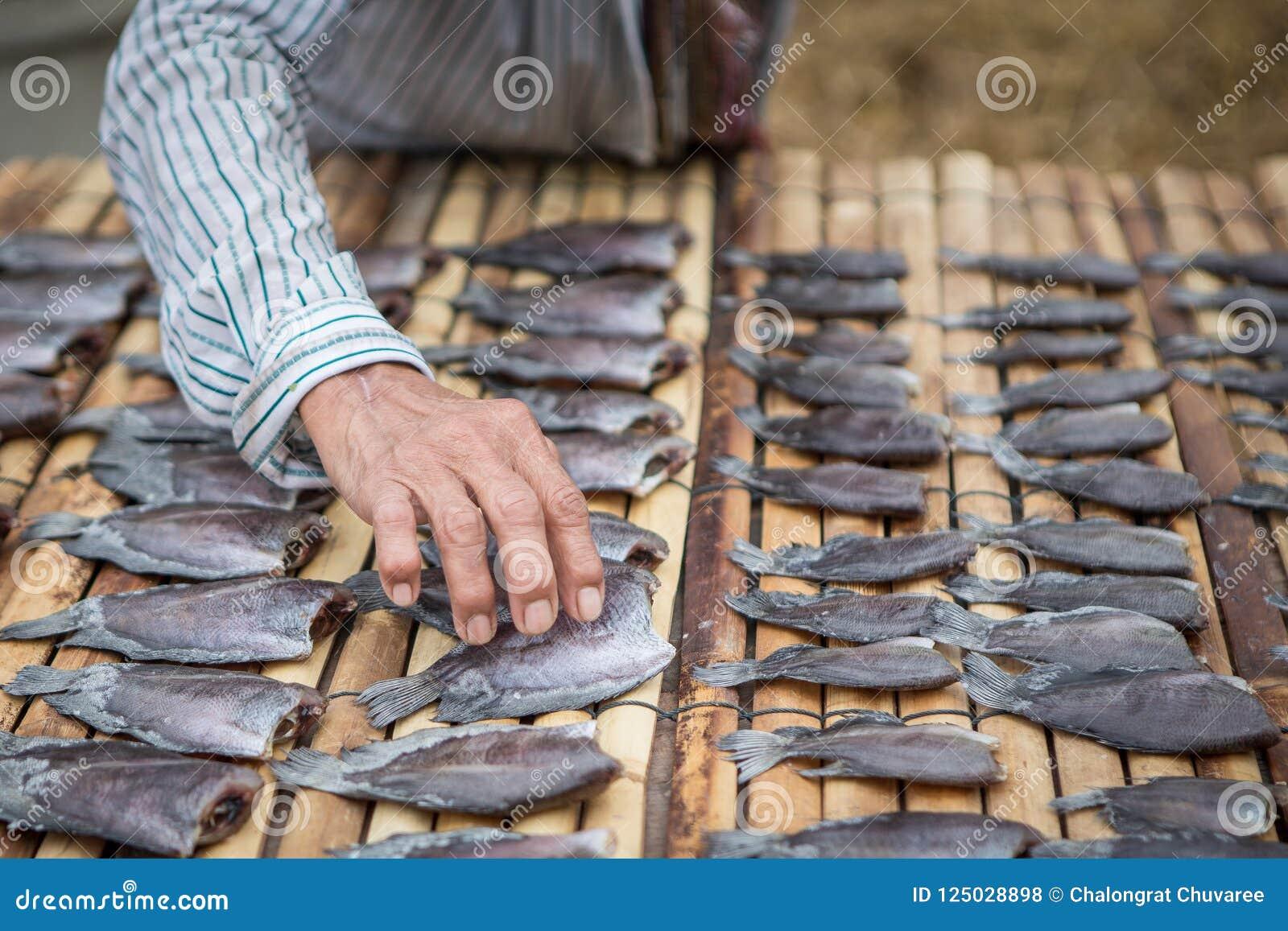 Las manos mantienen los pescados secos en una estera de bambú