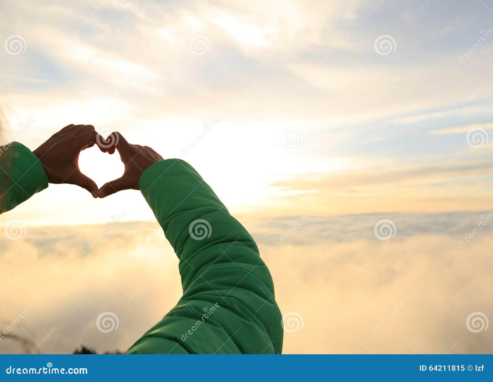 Las manos que hacen un corazón forman en la montaña de la salida del sol