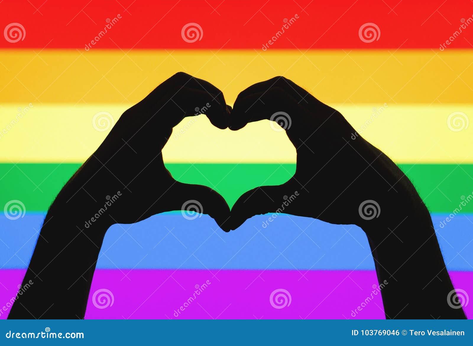 Las manos que muestran el corazón firman en bandera del orgullo gay y del arco iris de LGBT