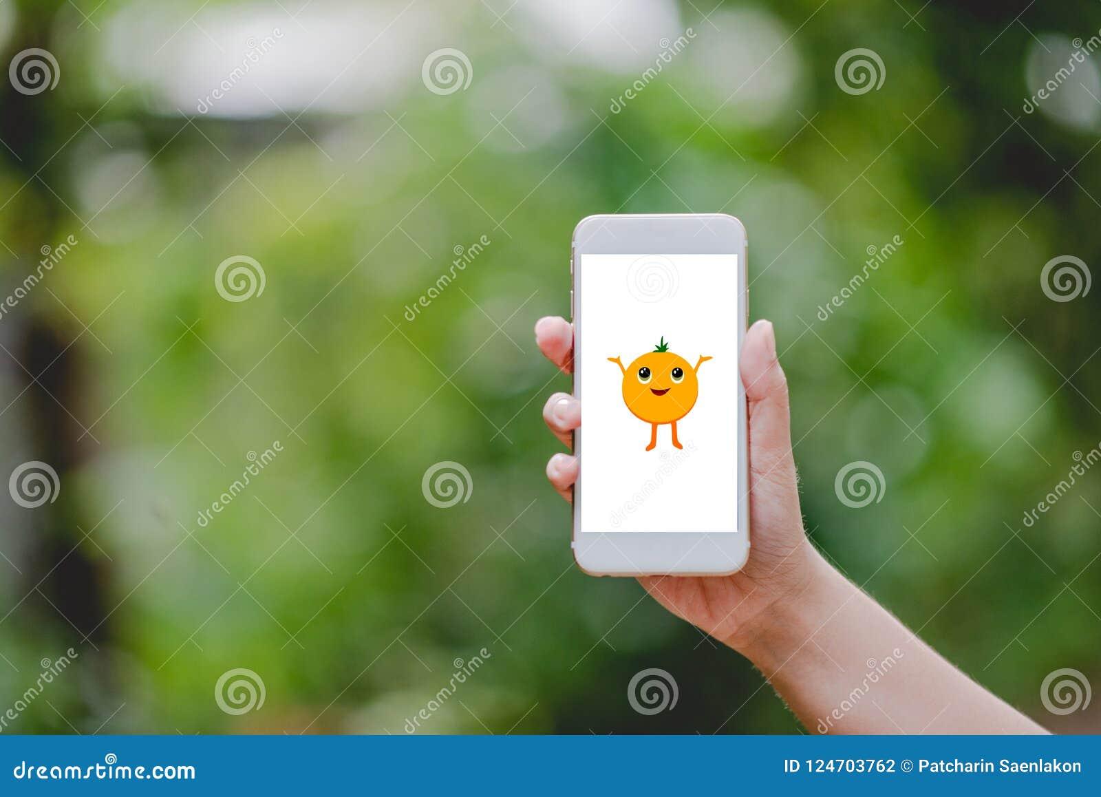 Las manos y pantalla anaranjada linda de los teléfonos la pequeña ponen verde la naturaleza Technolo