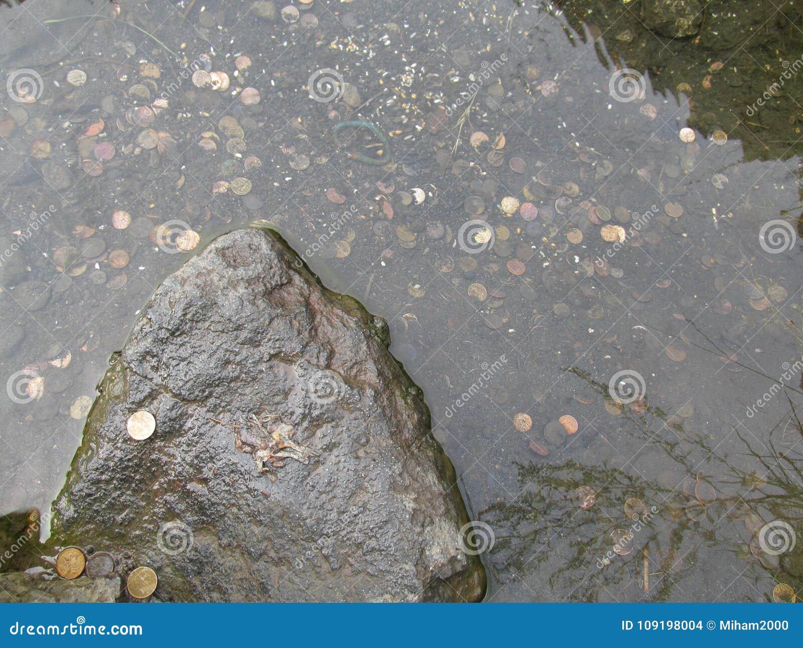 Las monedas en la fuente de agua