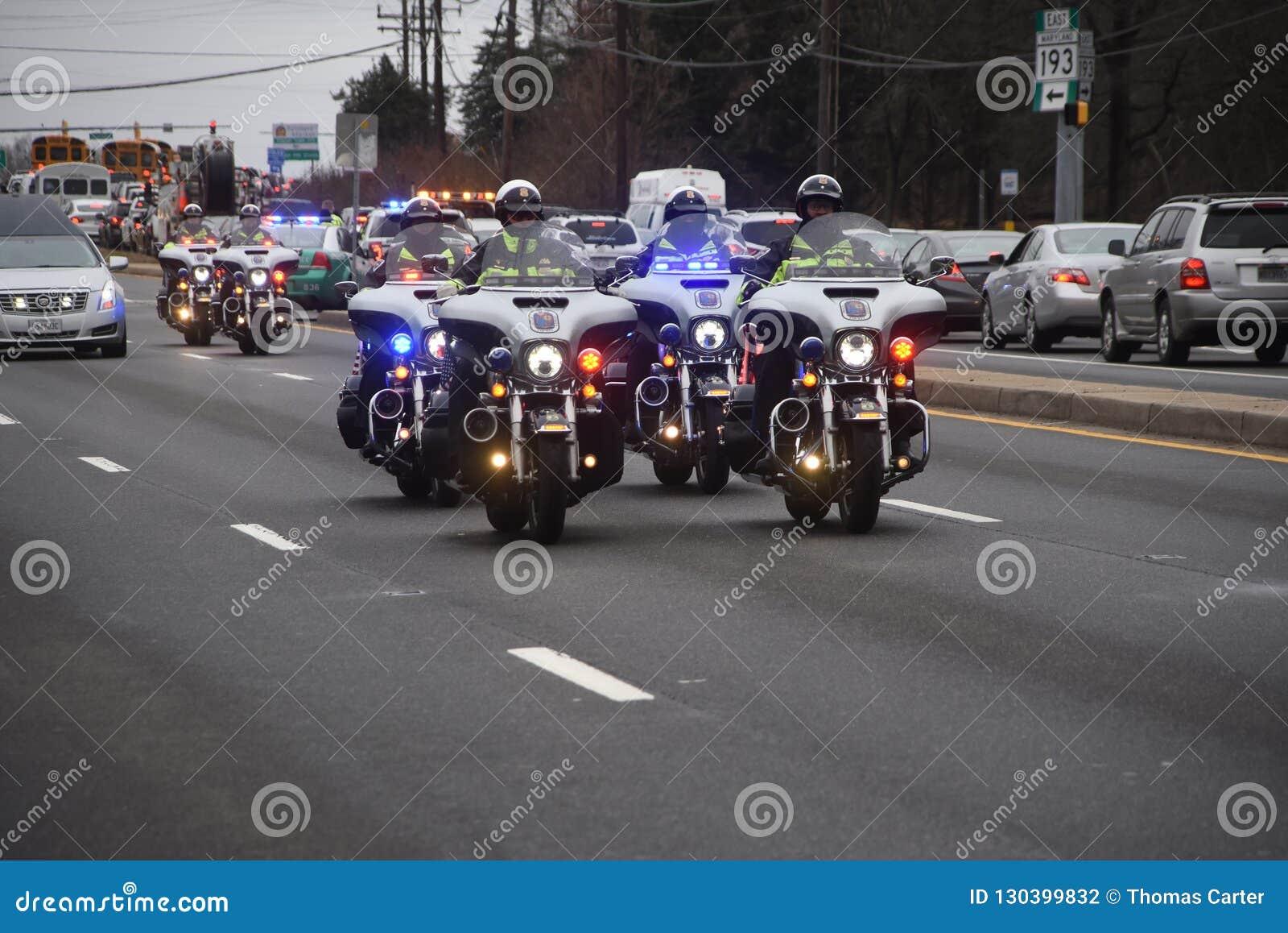 Las motocicletas de la policía escoltan un coche fúnebre
