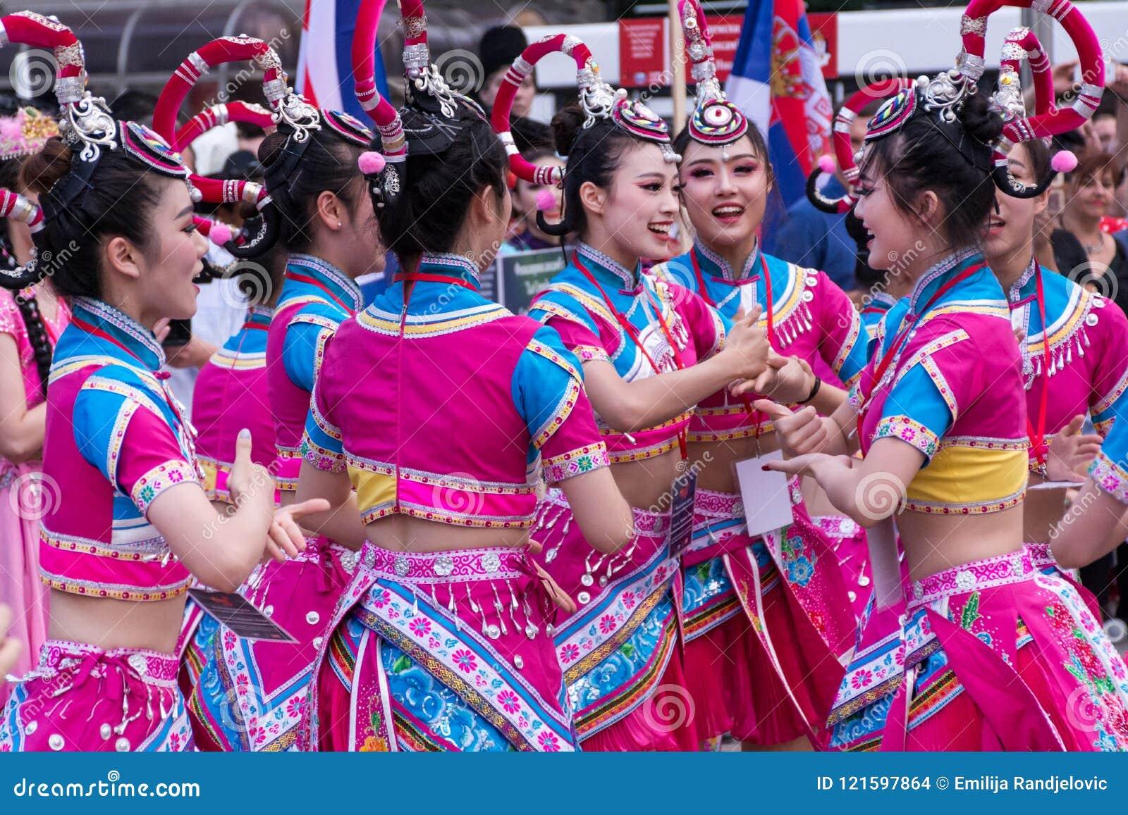 Las muchachas chinas jovenes bailan danza popular en trajes tradicionales