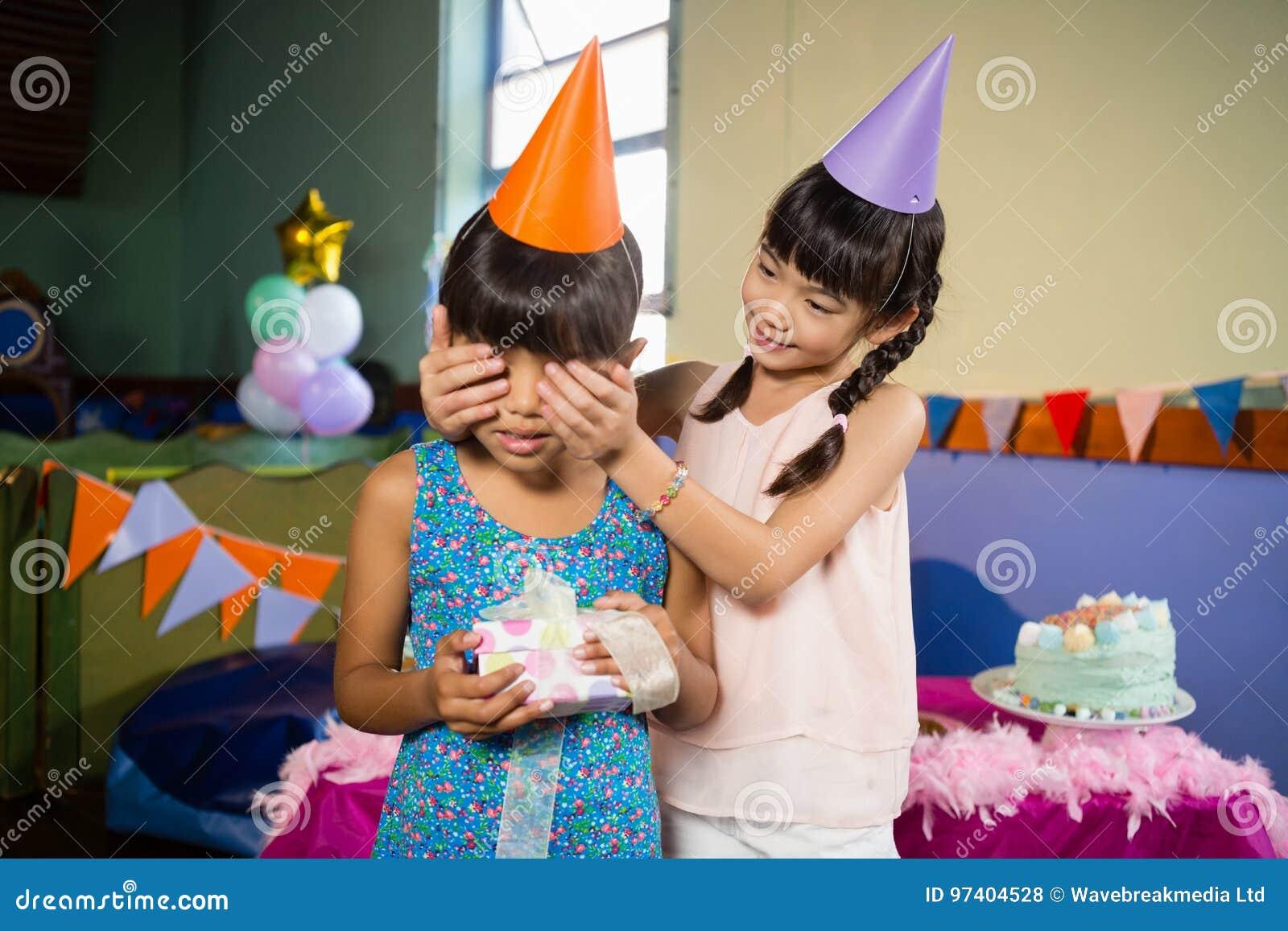 Las muchachas del cumpleaños de la cubierta de la muchacha observan y ofreciendo un regalo