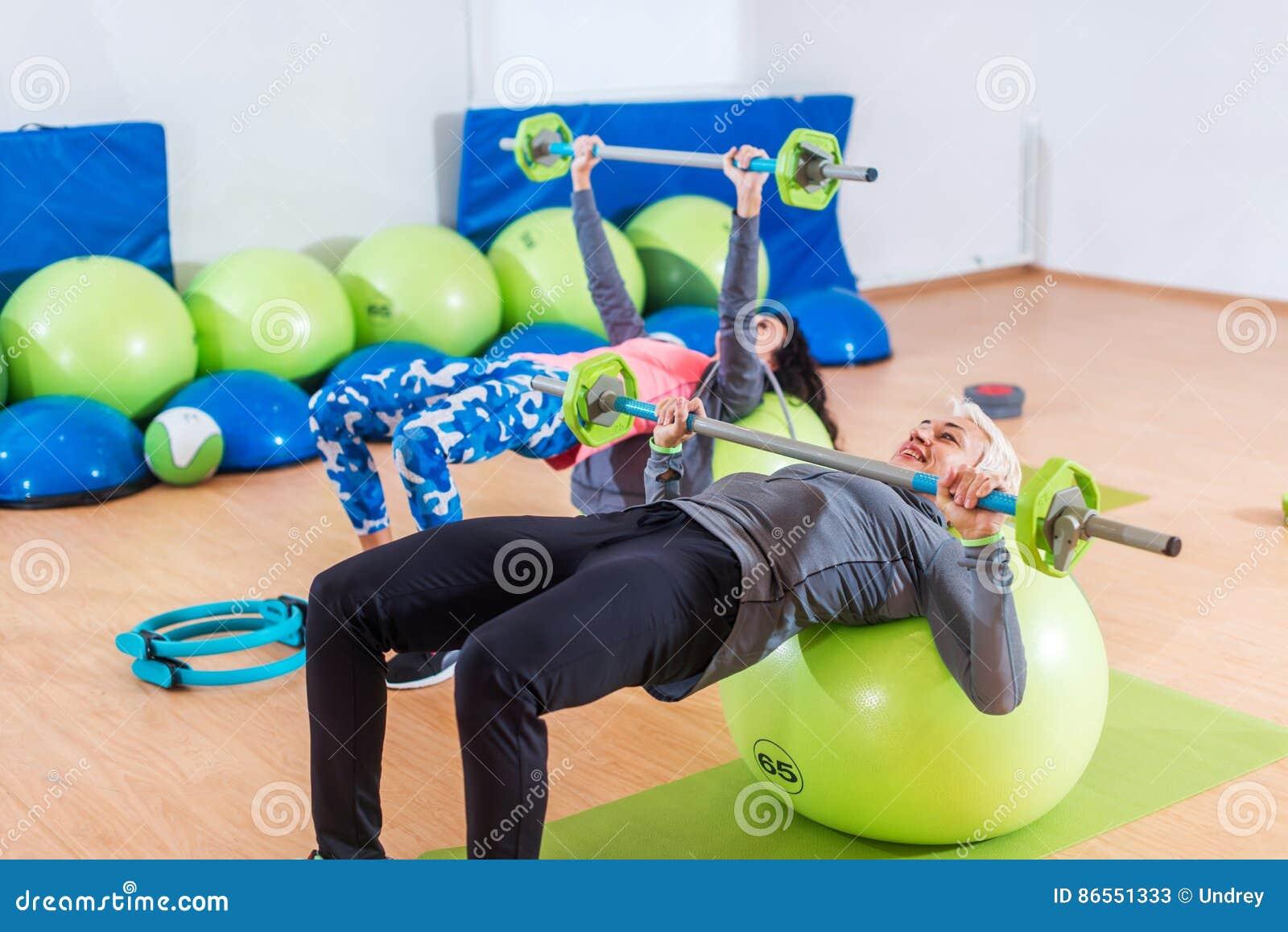 Las muchachas en los chándales que mienten en las bolas de la aptitud que hacen el pecho del barbell clavan un gimnasio Dos mujer