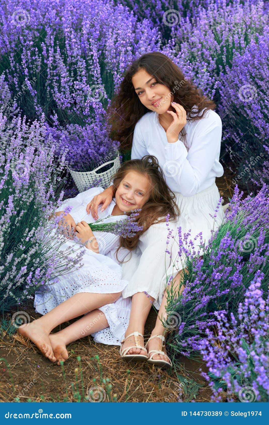 Las muchachas est?n en el campo de flor de la lavanda, paisaje hermoso del verano