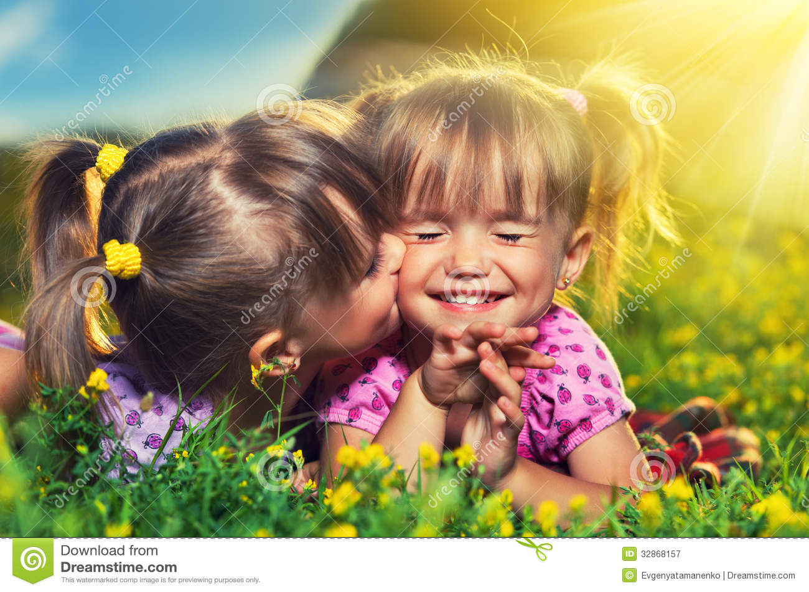 Las muchachas felices hermanan a las hermanas que se besan y que ríen en el verano
