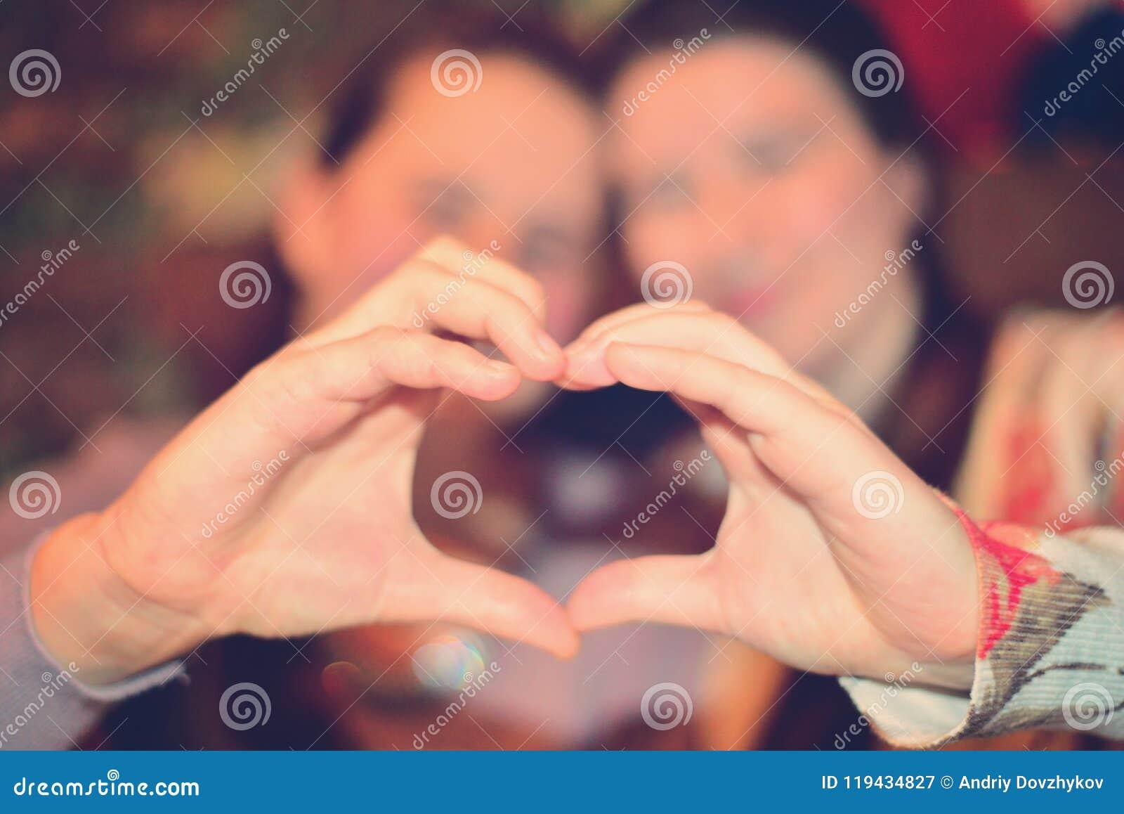 Las muchachas mueven de un tirón el corazón con sus manos El concepto de amor y de alegría