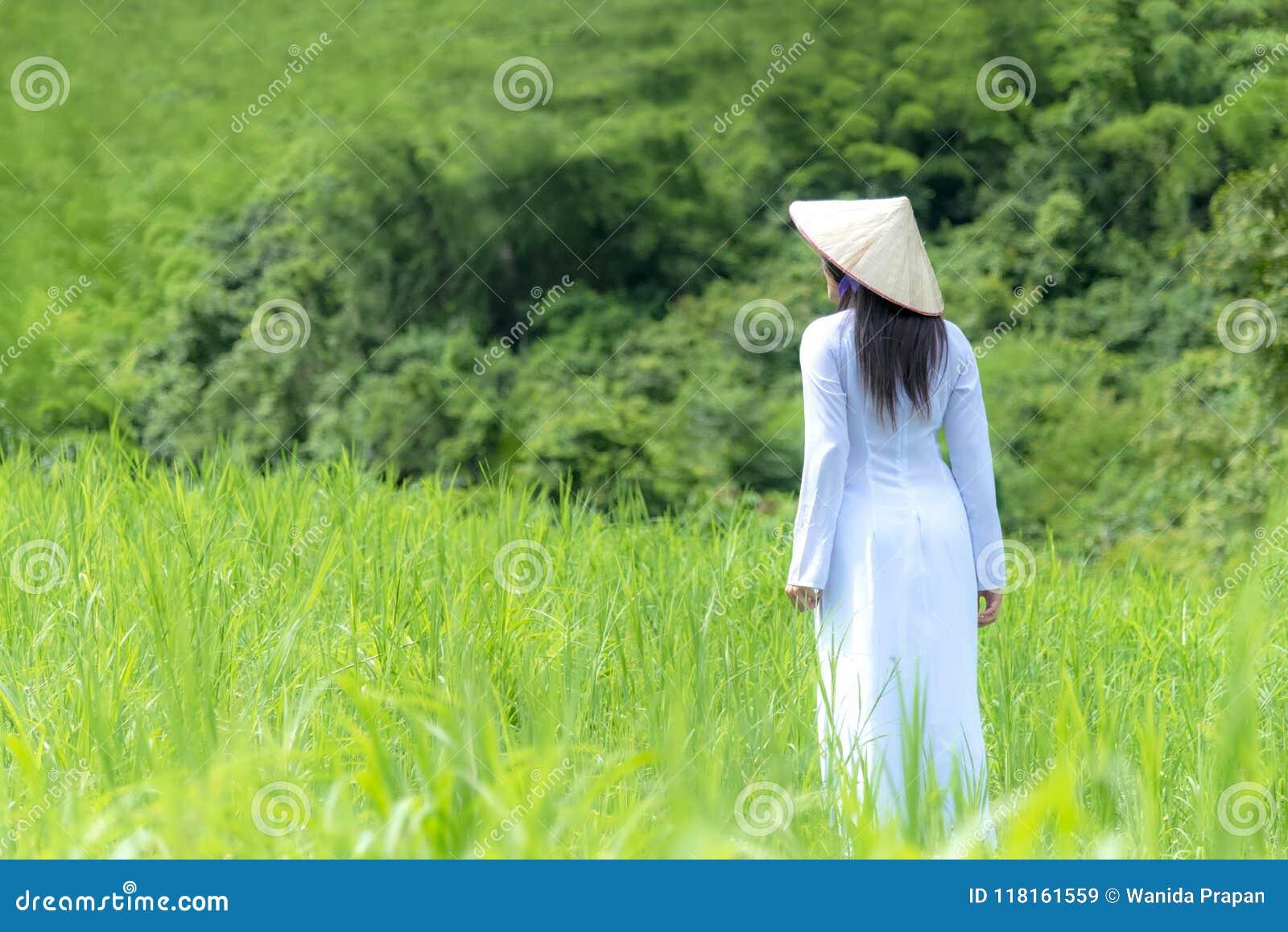Las mujeres asiáticas con el vestido tradicional de Ao-Dai Vietnam visten caminar de la mujer