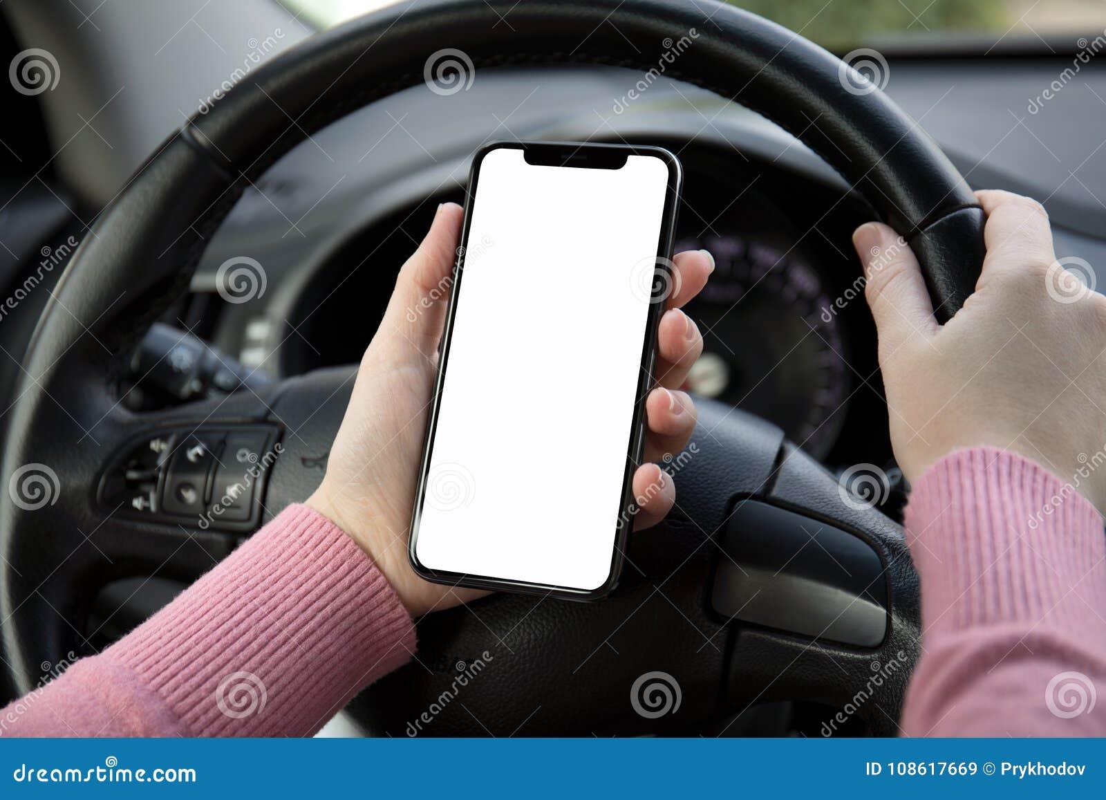 Las mujeres dan sostener el teléfono con la pantalla en el coche