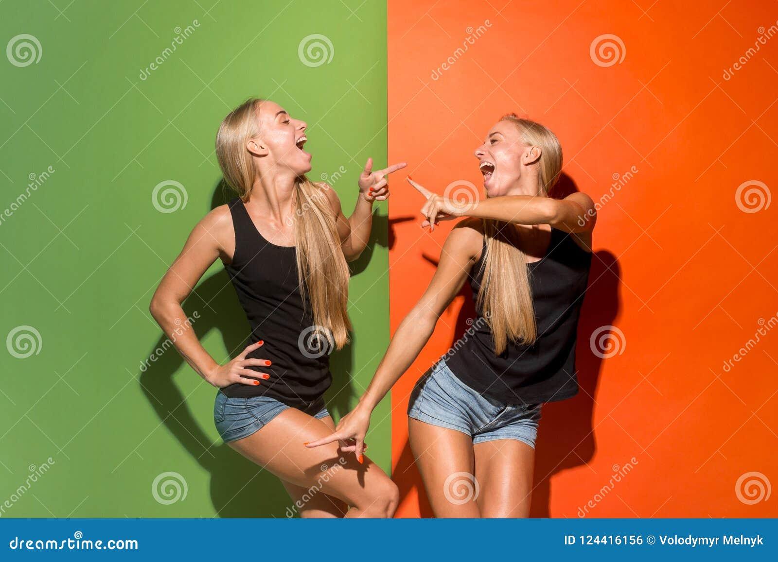 Las mujeres de negocios felices que se colocan y que sonríen