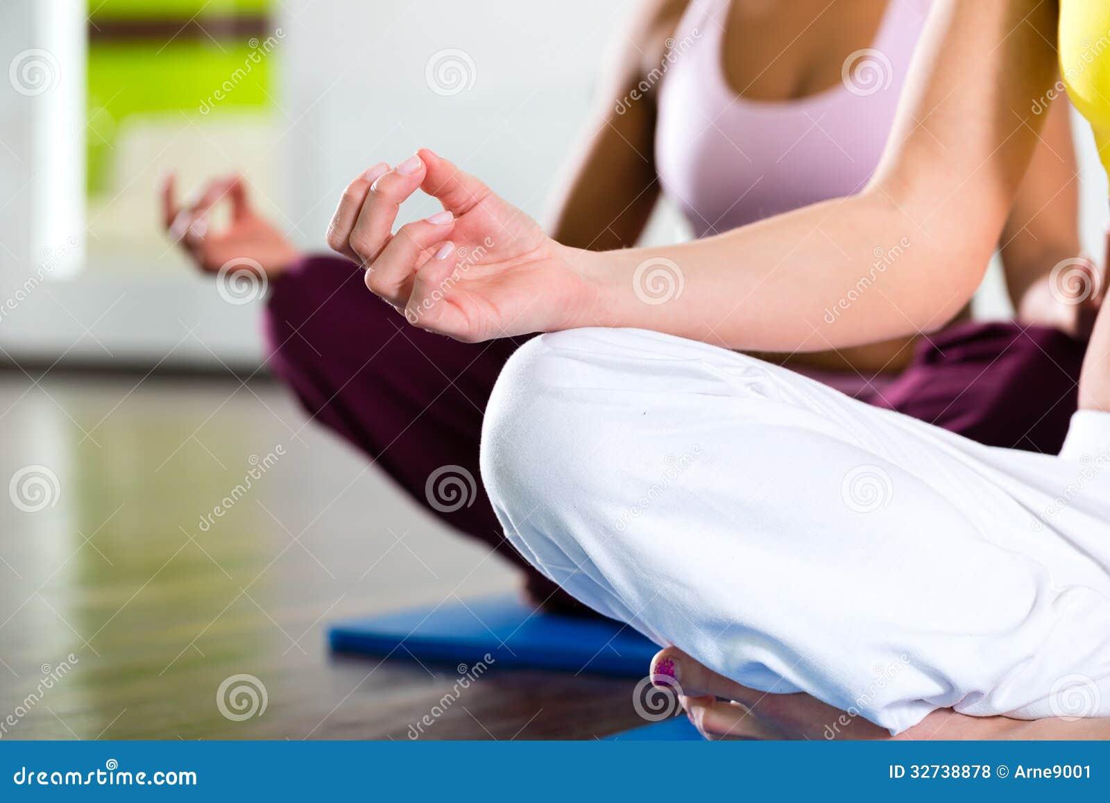 Las mujeres en el gimnasio que hace yoga ejercitan para la aptitud