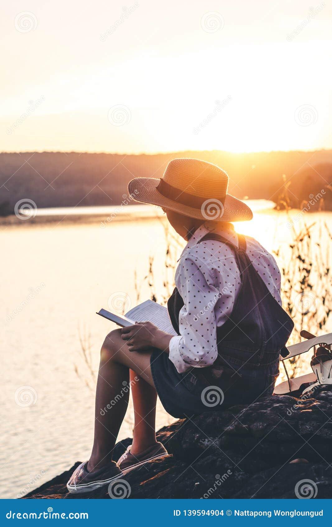 Las mujeres en invierno se sientan leyeron el libro preferido en el día de fiesta, muchacha del concepto que lee un libro
