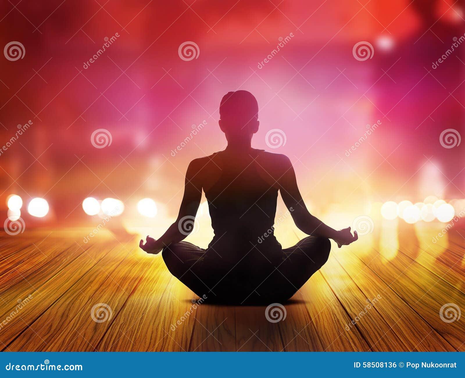 Las mujeres están meditando en la noche y los rayos de la luz púrpuras en la ciudad