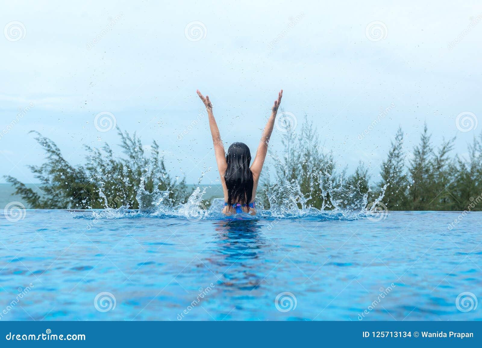 Las mujeres felices de la forma de vida se relajan y gozan en la piscina cerca de la playa Las mujeres juntas el verano y vacacio