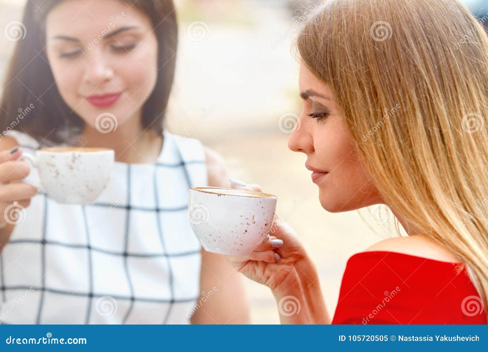 Las mujeres jovenes atractivas beben el café en ciudad del verano