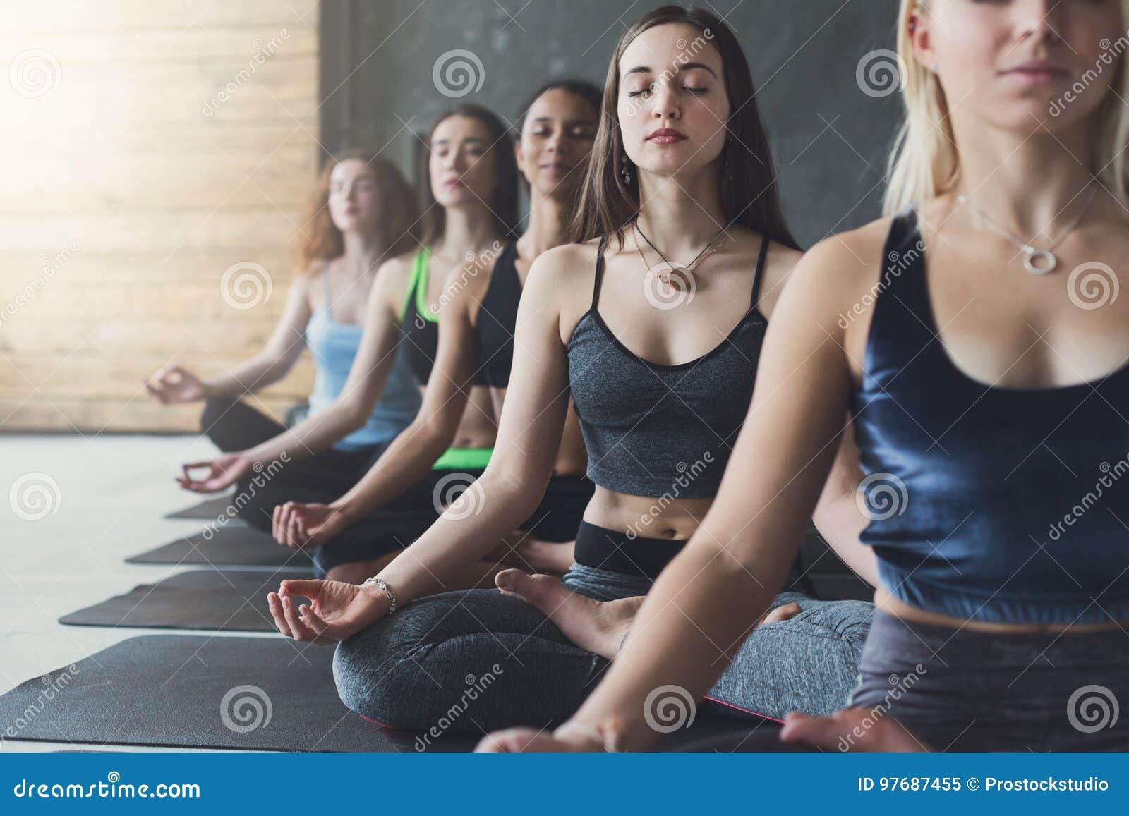 Las mujeres jovenes en yoga clasifican, relajan actitud de la meditación