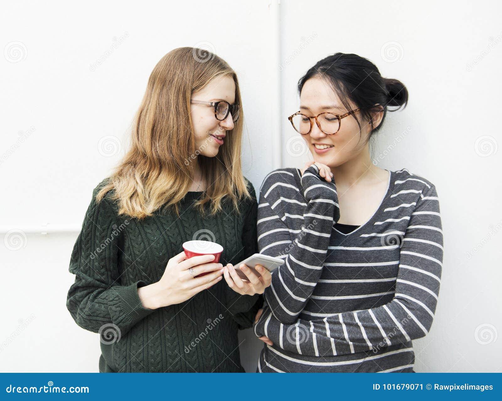 Las mujeres jovenes están utilizando el teléfono móvil
