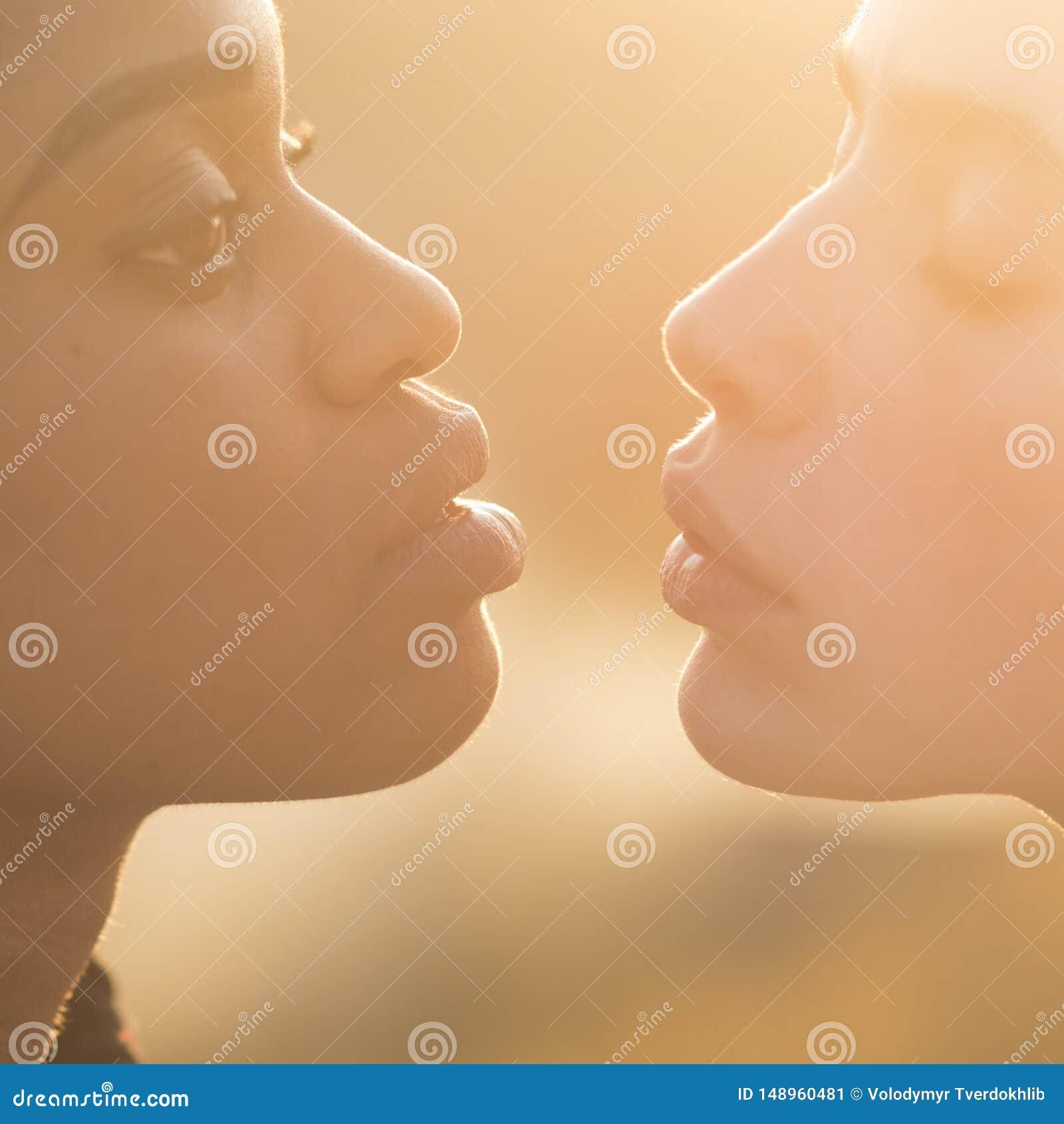 Las mujeres jovenes ponen mala cara los labios para el beso, maquillaje