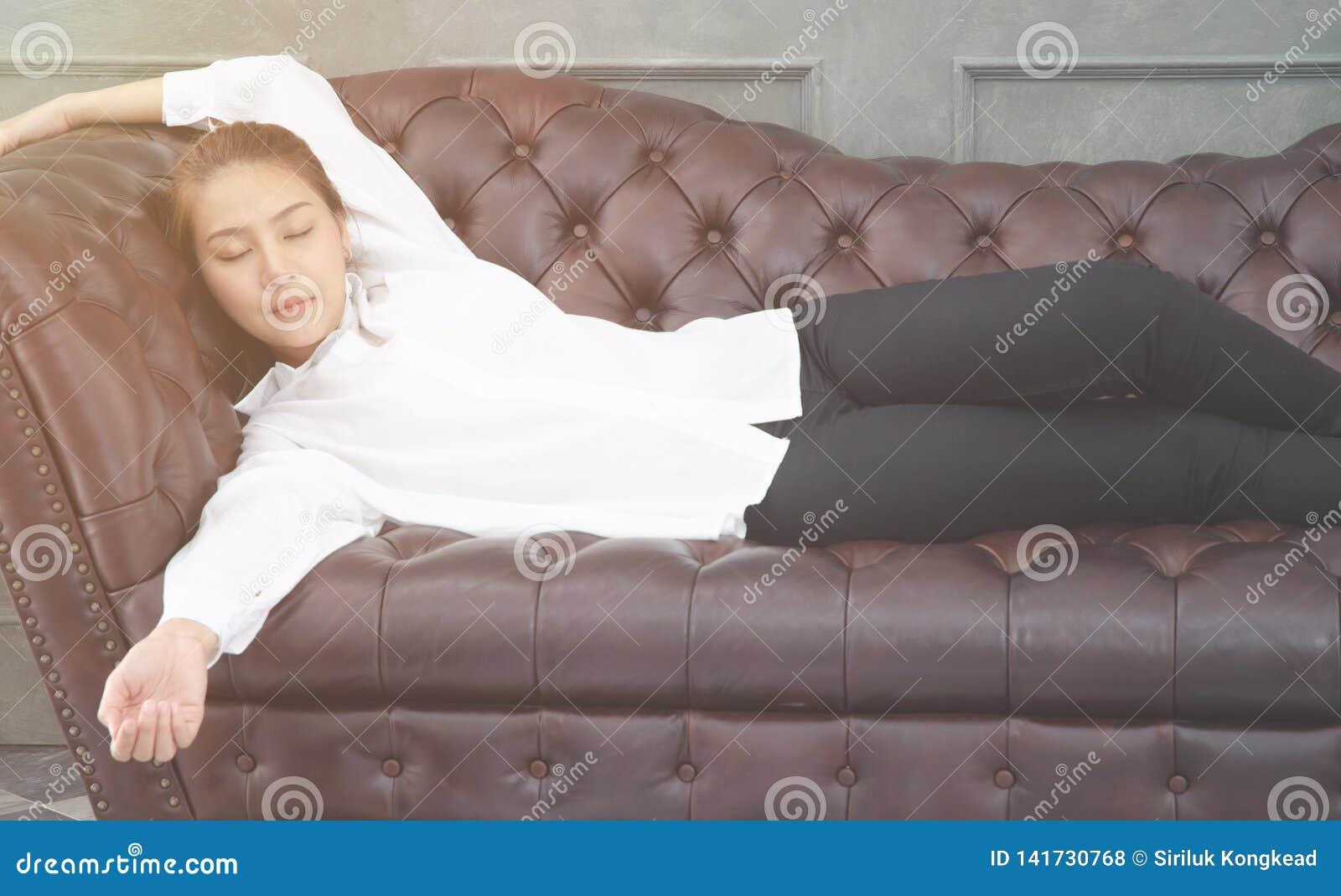 Las mujeres que llevan una camisa blanca ella está durmiendo en el sofá