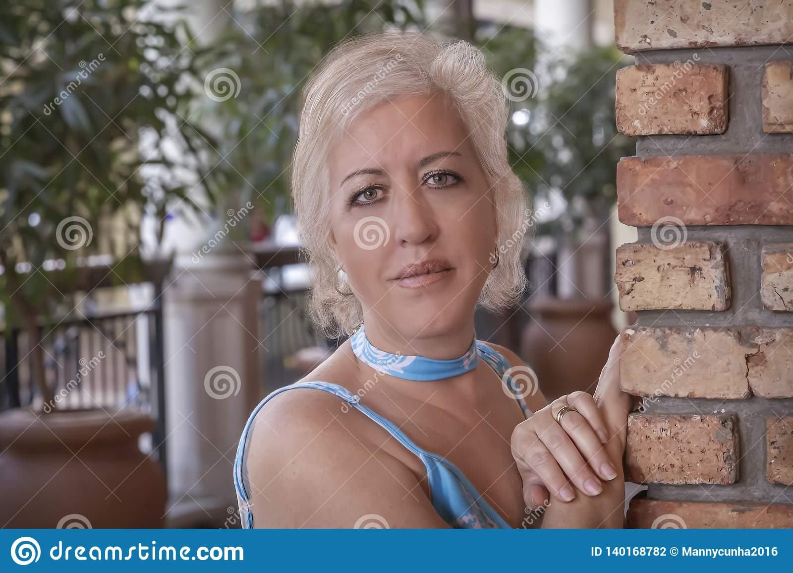 Las mujeres rubias maduras se inclinan con las manos en una pared de ladrillo que mira la cámara con una sonrisa agradable