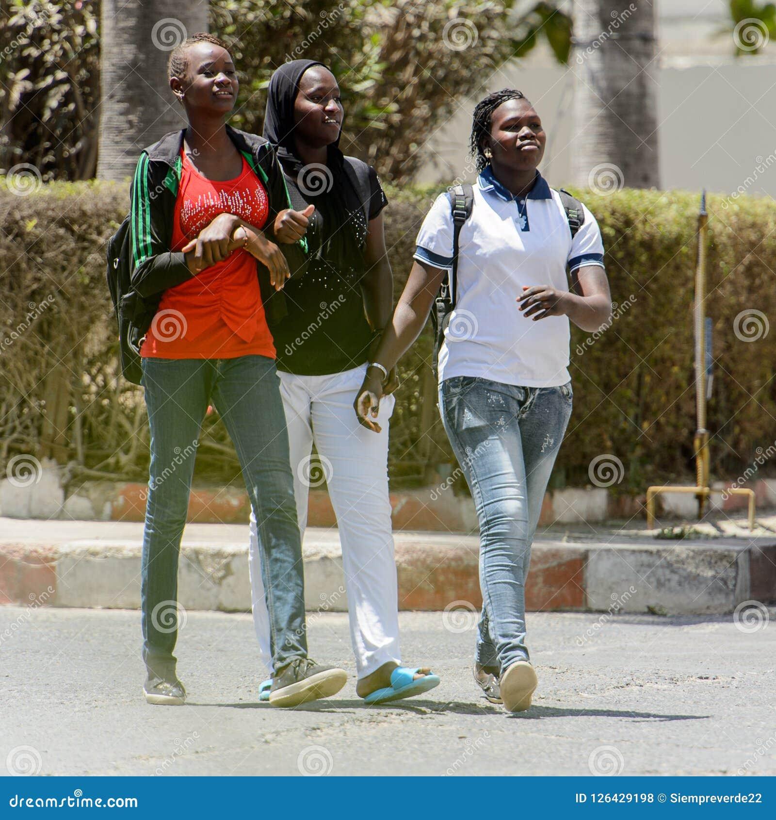 Las mujeres senegalesas no identificadas caminan a lo largo de la calle en el centavo