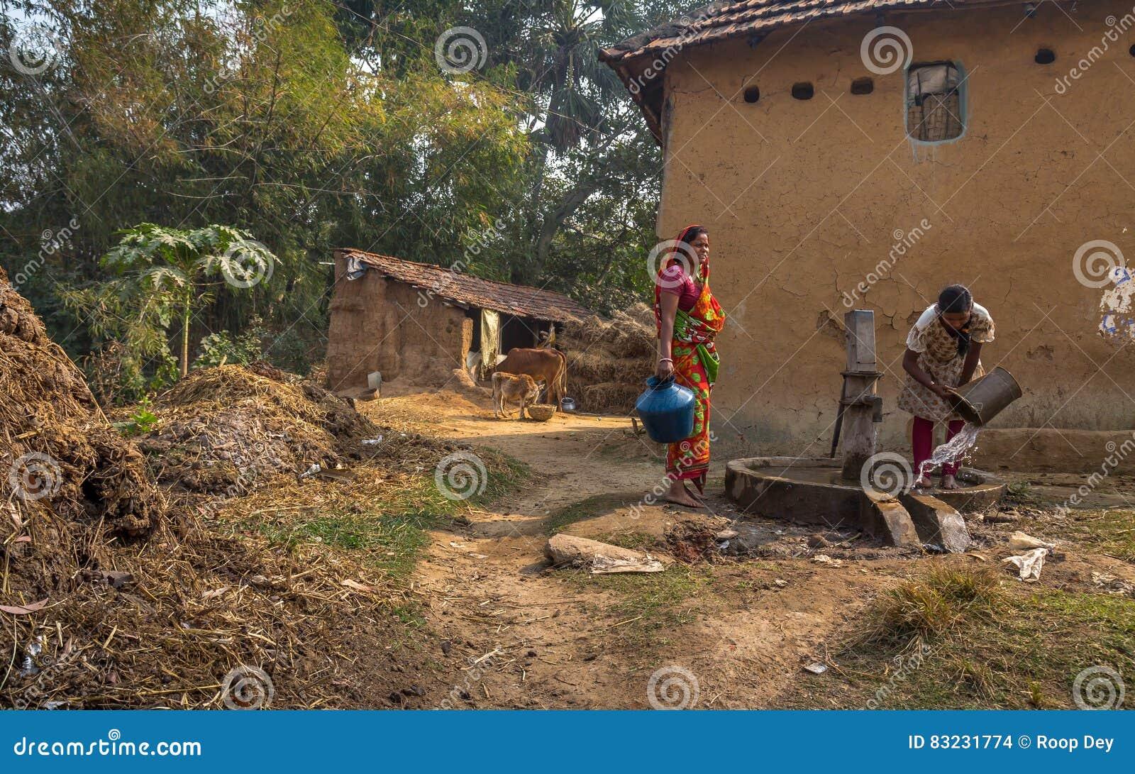 Las mujeres tribales extraen el agua de un tubo profundo bien en un pueblo indio rural