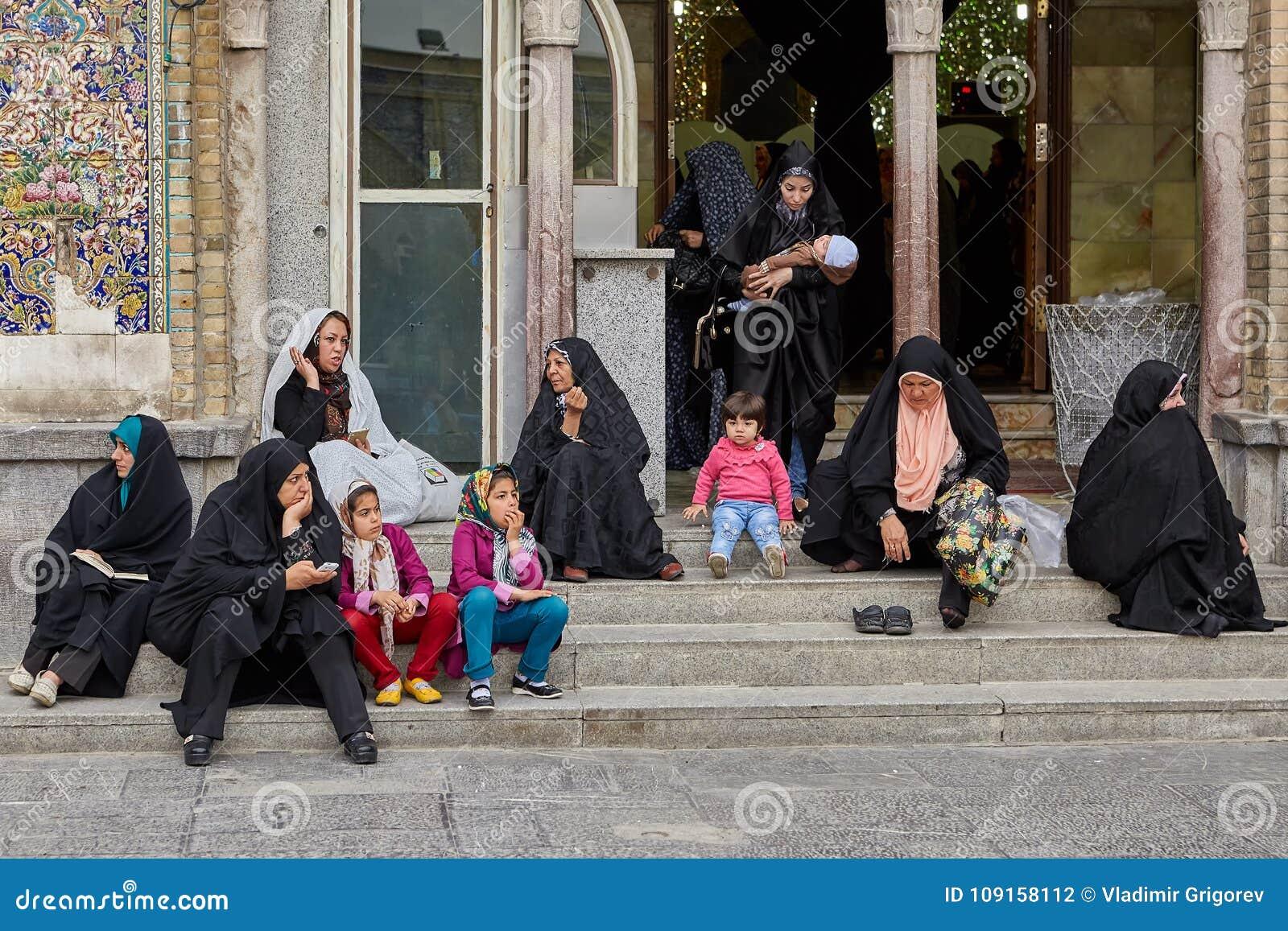 Las mujeres y los niños iraníes se sientan cerca de la mezquita, Teherán, Irán