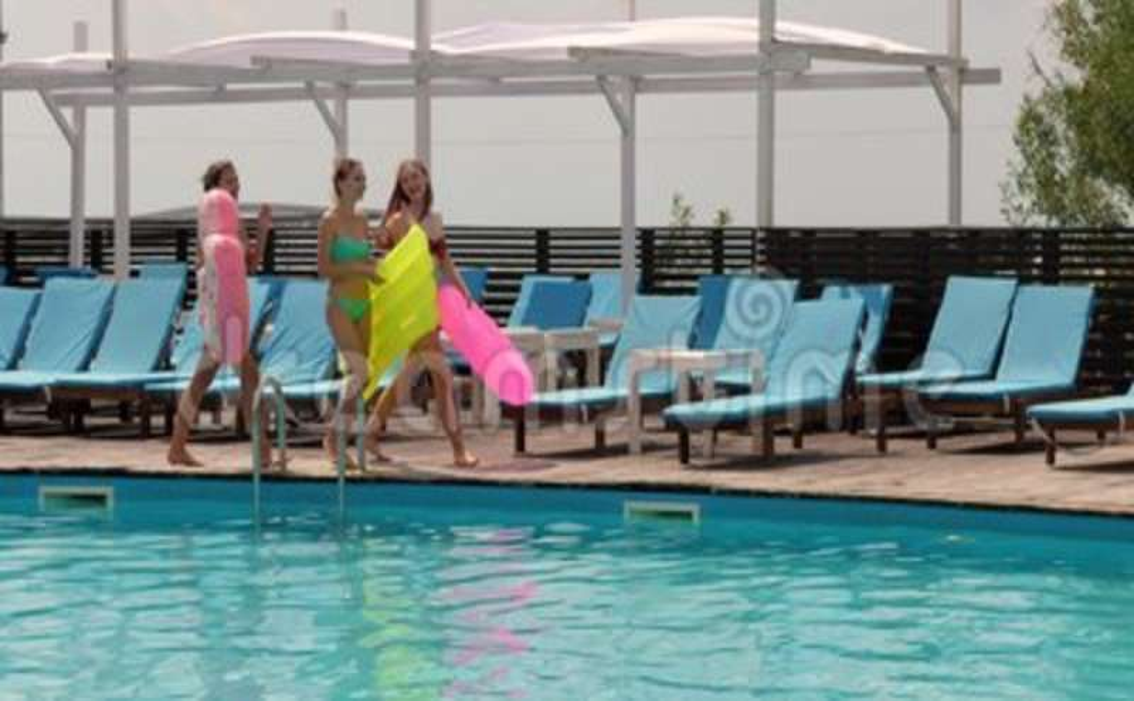 b11c44858be4 Las novias en bañador van a lo largo del embarcadero de madera en la  piscina del fondo con agua azul, mujeres jovenes.