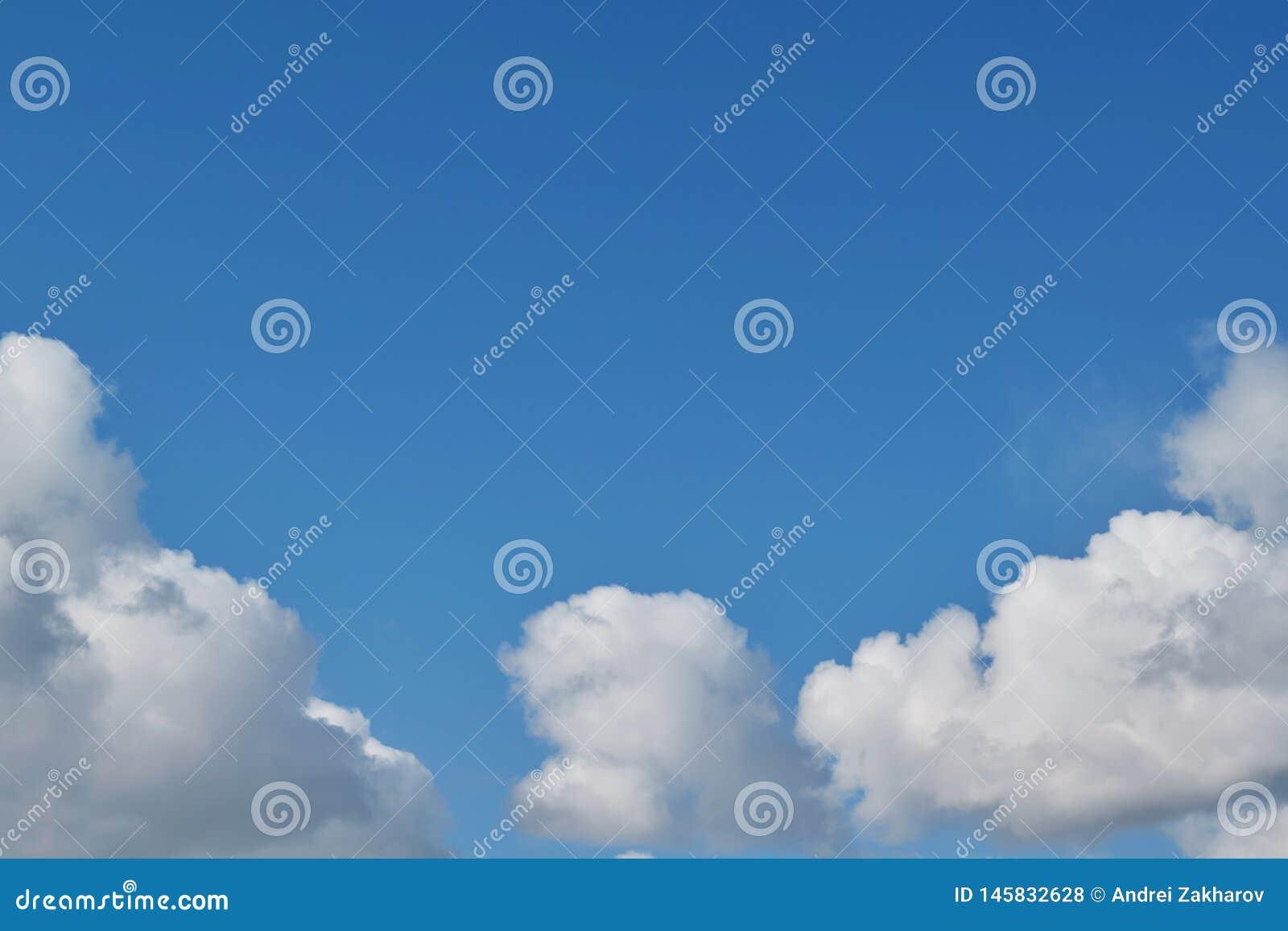 Las nubes de cúmulo blancas mullidas de los cielos azules arreglaron bajo la forma de arco