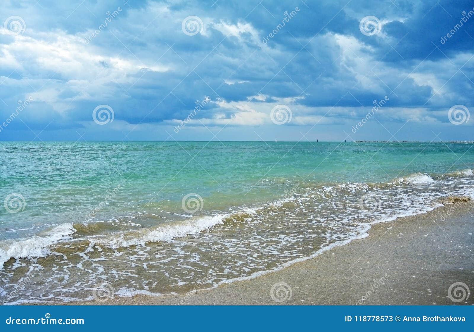 Las nubes de lluvia oscuras sobre el mar y la arena de la turquesa varan