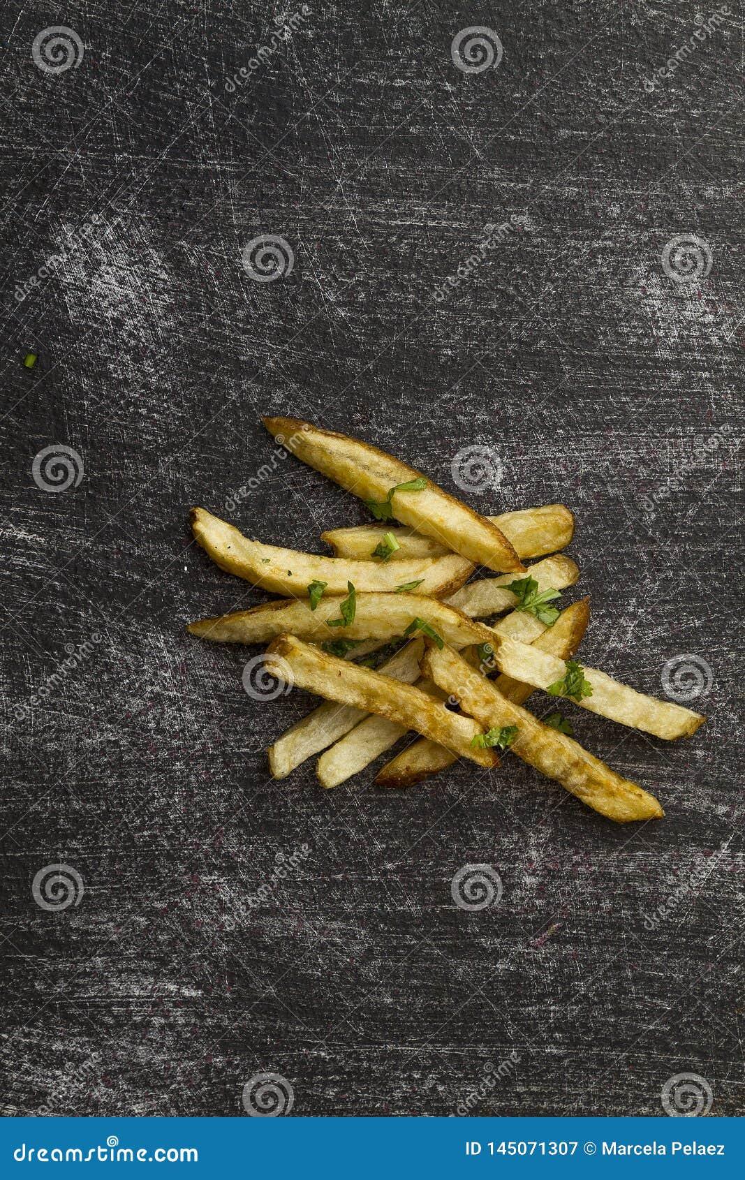 Las patatas fritas ventilan el plato exterior frito en la tabla gastada negra