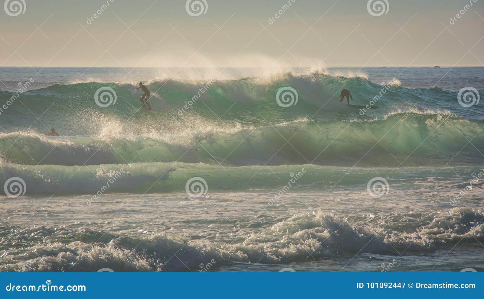 Las personas que practica surf montan una onda grande en condiciones ventosas
