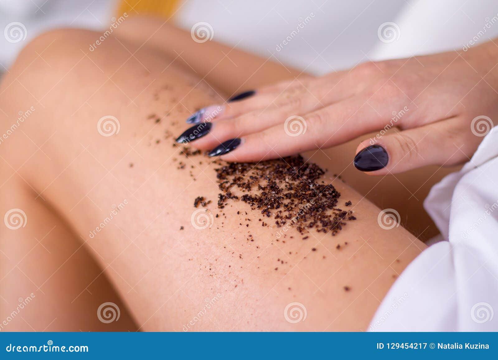 Las piernas de la mujer del primer con masaje del café friegan Cosmetología, preparación, productos cosméticos del balneario, bel