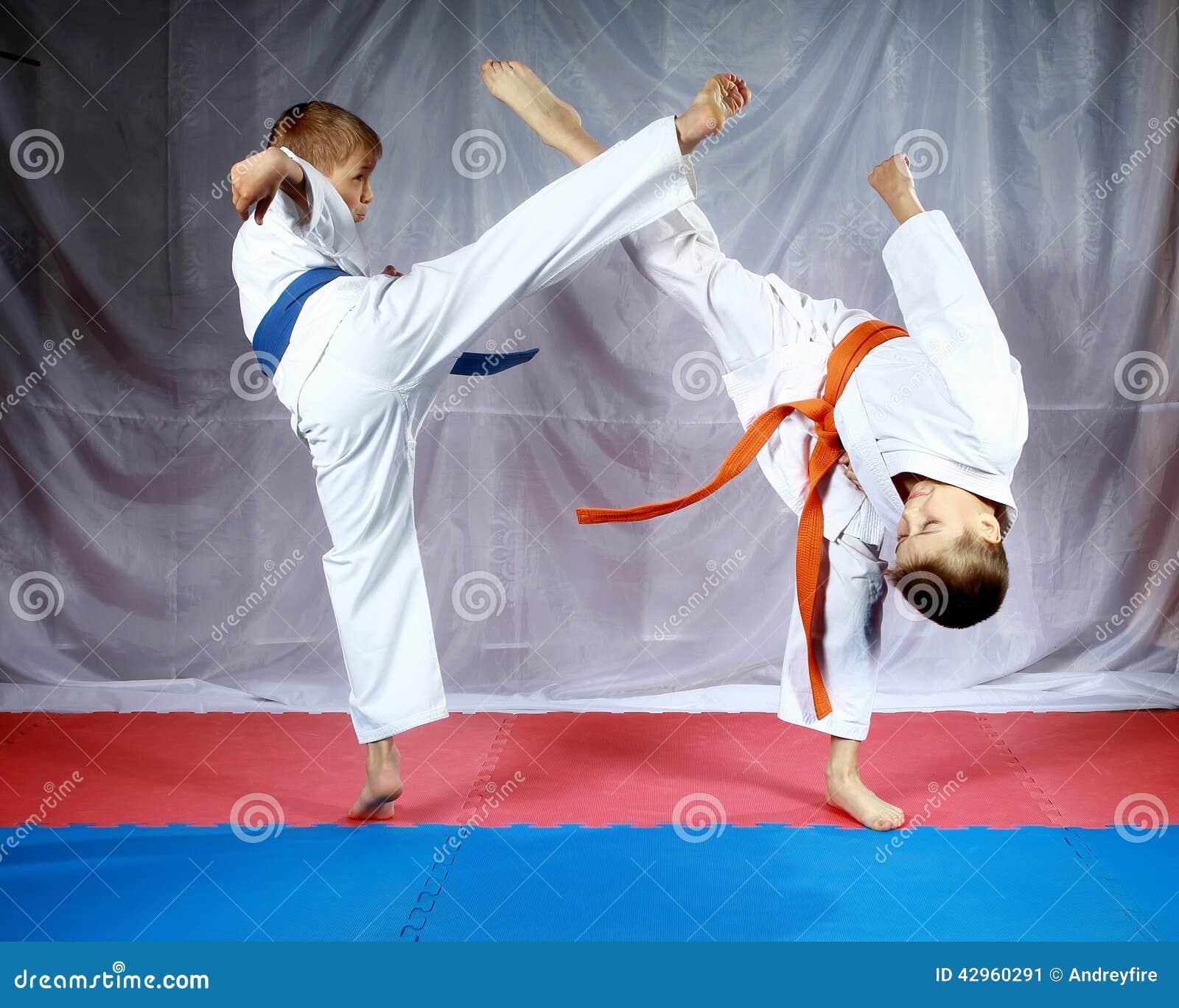 Las piernas de los soplos para encontrarse están batiendo a atletas en karategi