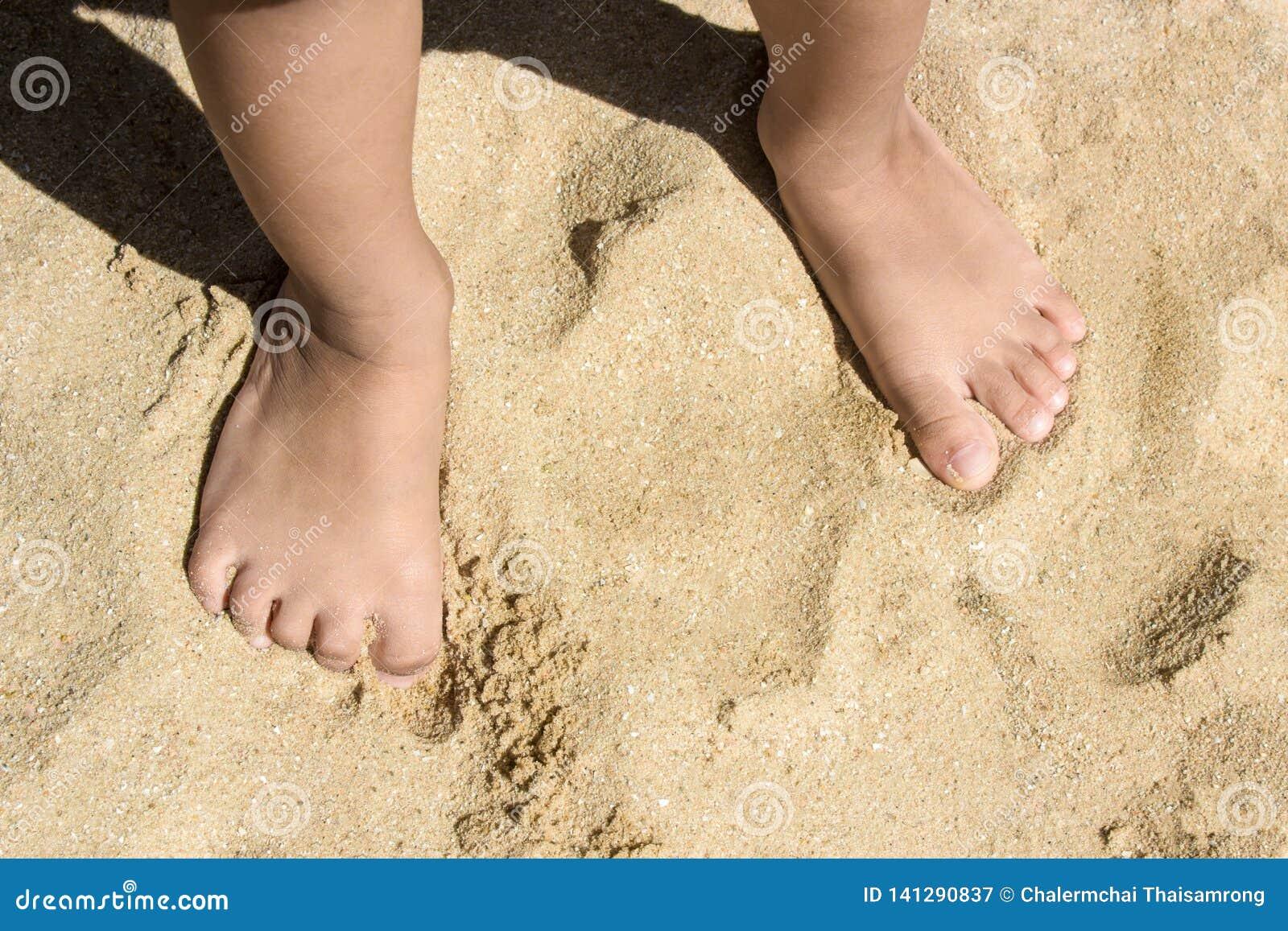 Las piernas de niños se colocan en la playa con el espacio de la copia