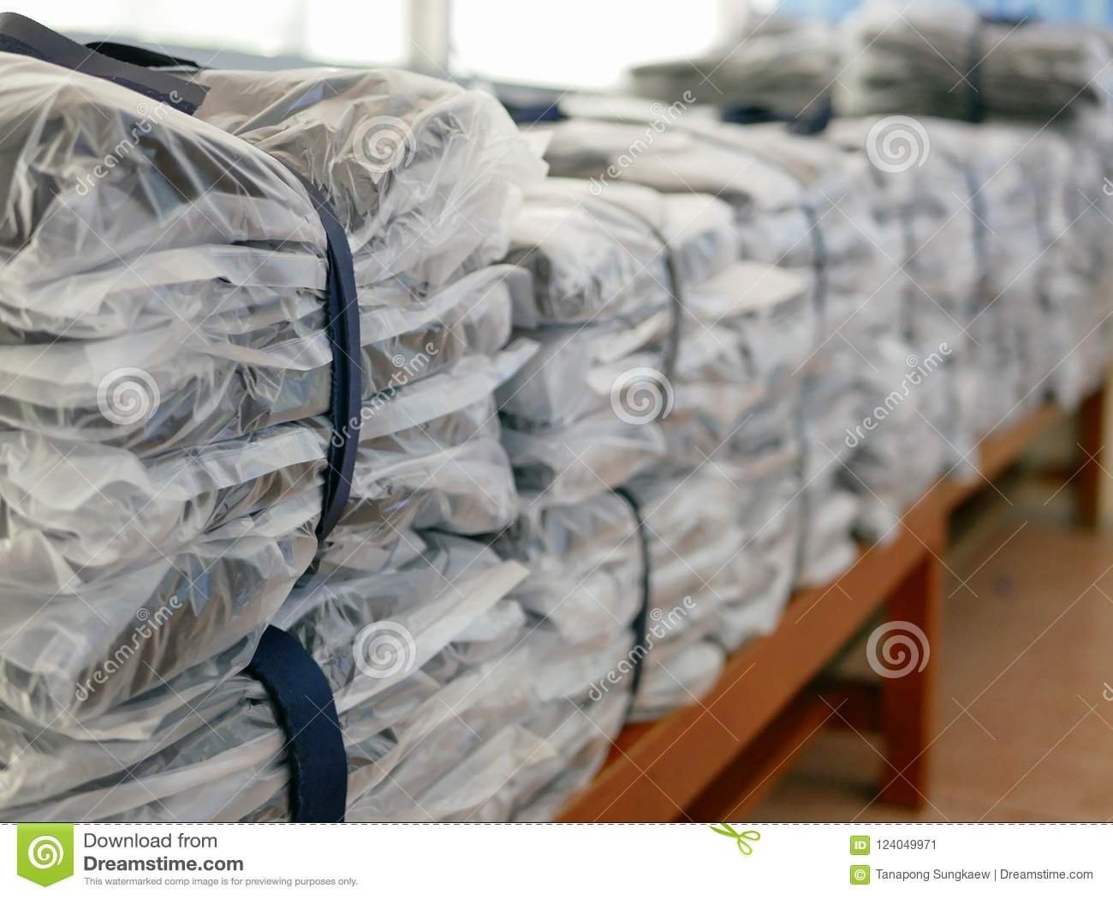 Las pilas de ropa embalaron en las bolsas de plástico listas para ser enviado/para ser distribuido
