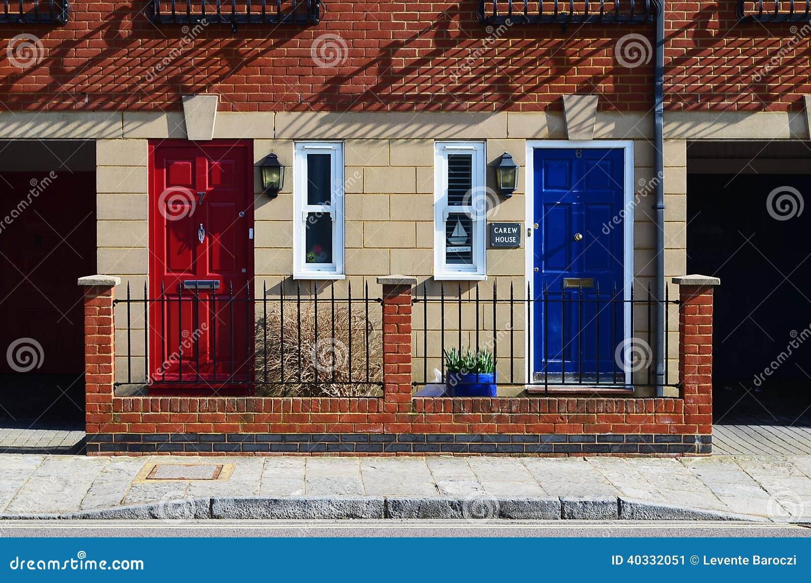 Las puertas vecinas rojas y azules en ladrillo emparedaron la casa del equipo