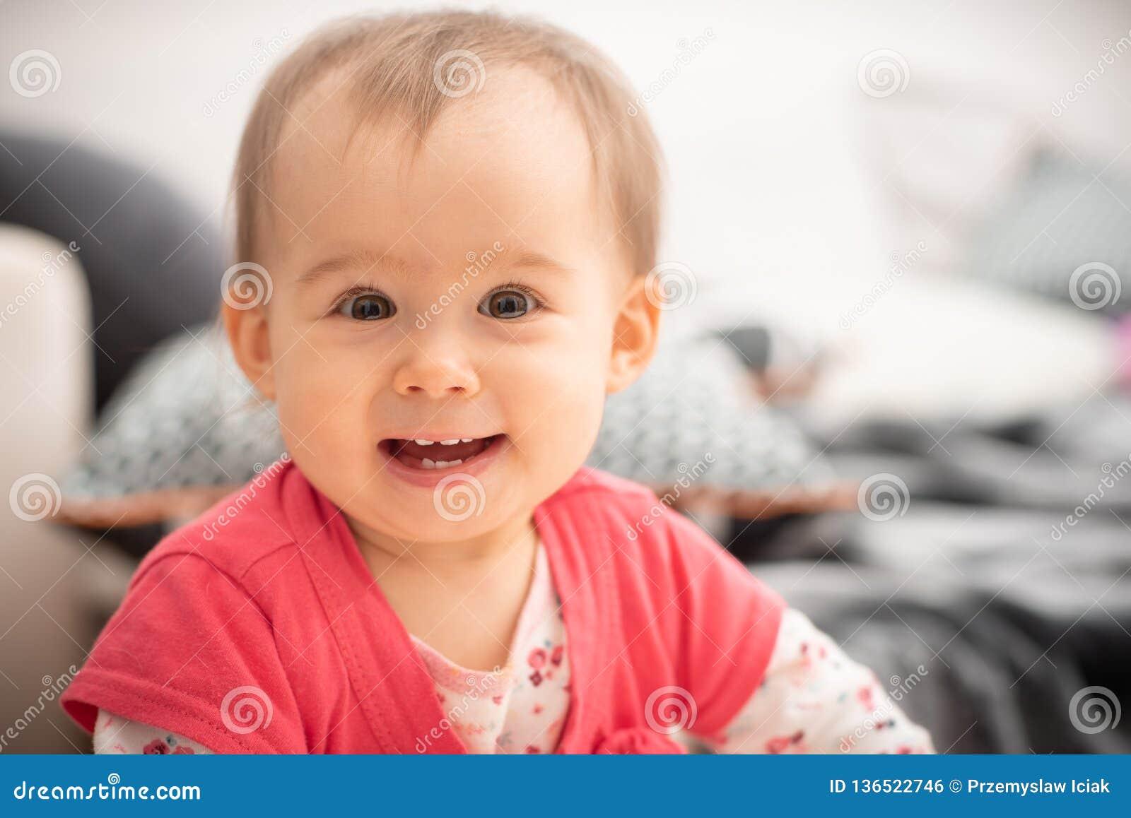 Las risas de 1 año lindas del bebé en ojos marrones grandes de la cámara y sonrisa amplia con nuevo echan los dientes, concepto d