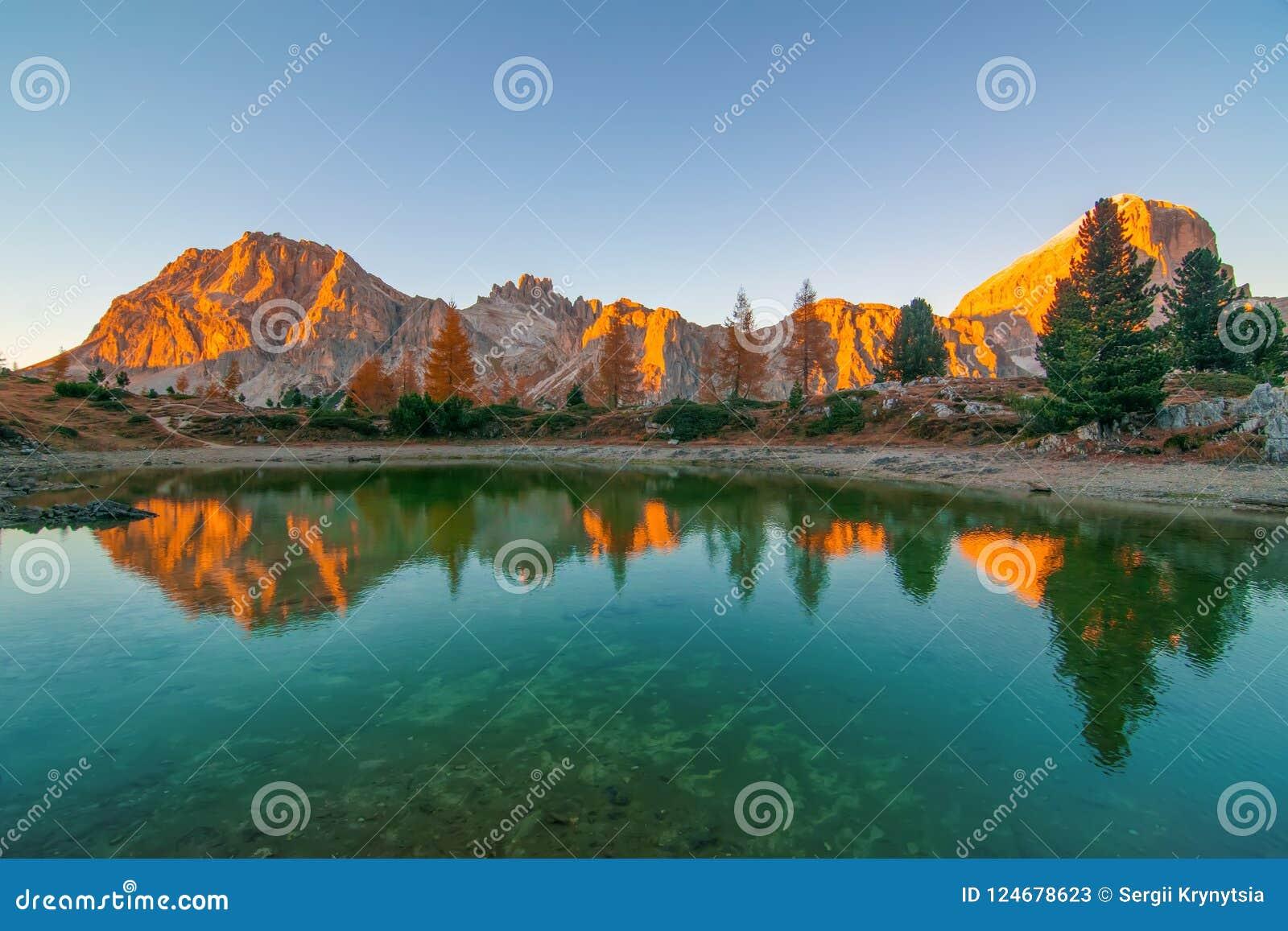 Las rocas de la montaña y los árboles del otoño reflejaron en el agua del lago en la puesta del sol, montañas de la dolomía, Ital