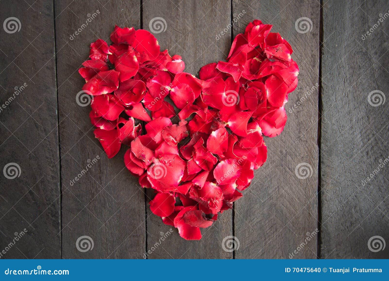 Las rosas rojas del pétalo formaron como un corazón en el fondo de madera,