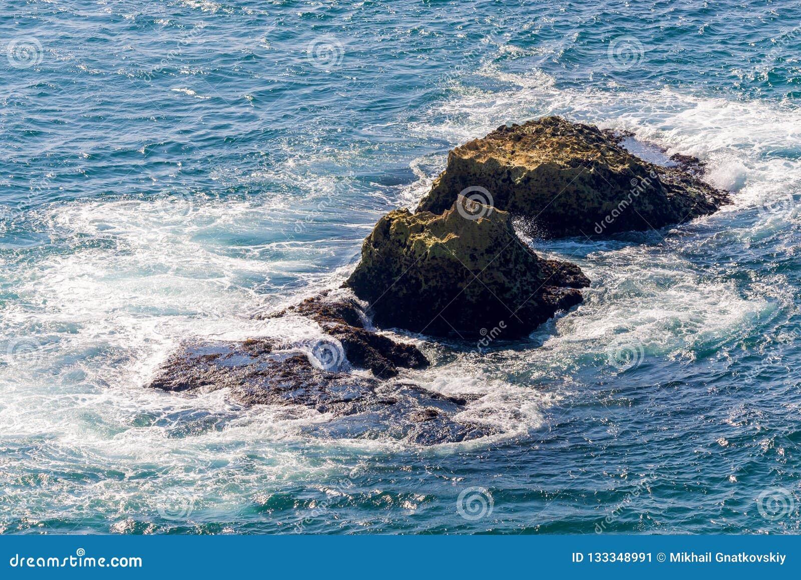 Las roturas de la onda del mar en rocas de la playa ajardinan Las ondas del mar se estrellan y salpican en rocas Fractura de la o