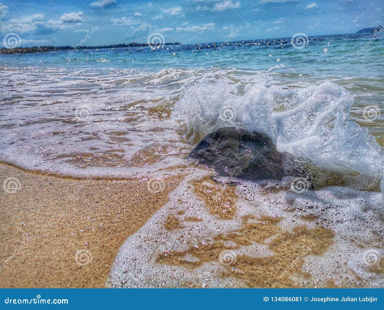 Las roturas hermosas de la onda a la orilla y a la ella llamaron chapoteante