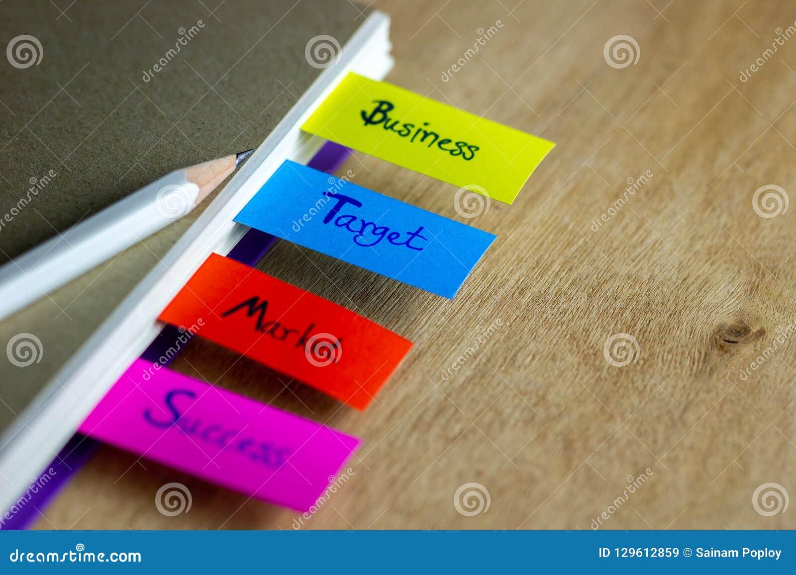 Las señales coloridas se escriben para el negocio, blanco, mercado, éxito, y tienen un lápiz blanco