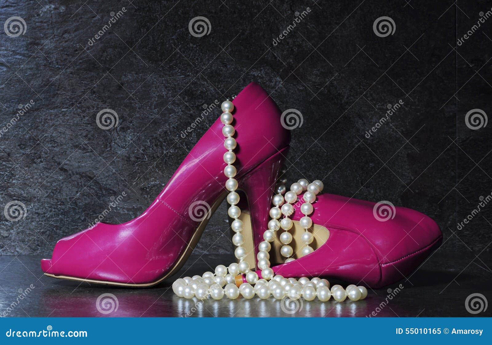 Las señoras pican los tacones altos con el filamento largo de las perlas blancas