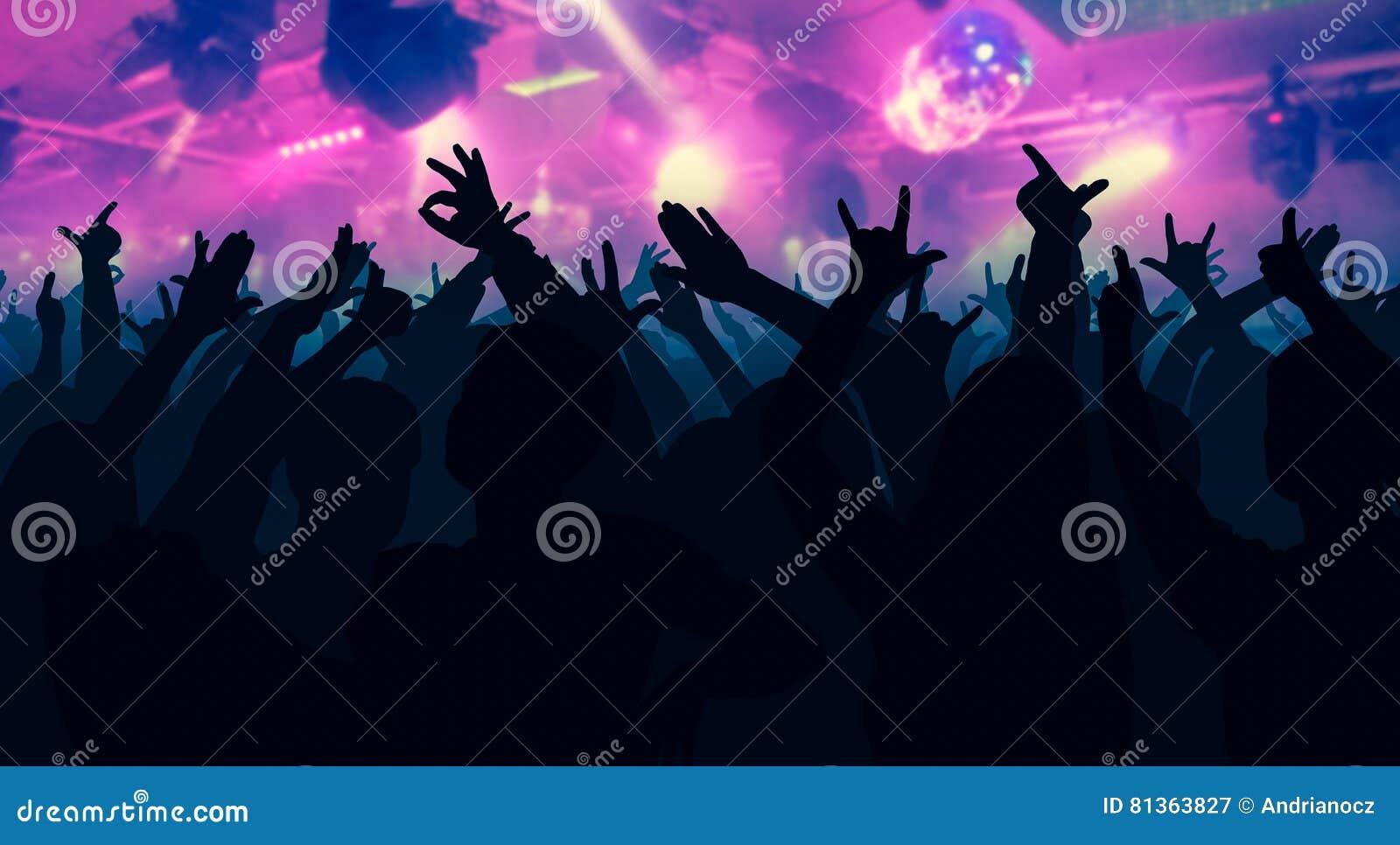 Las siluetas de la gente del baile delante de la etapa brillante se encienden
