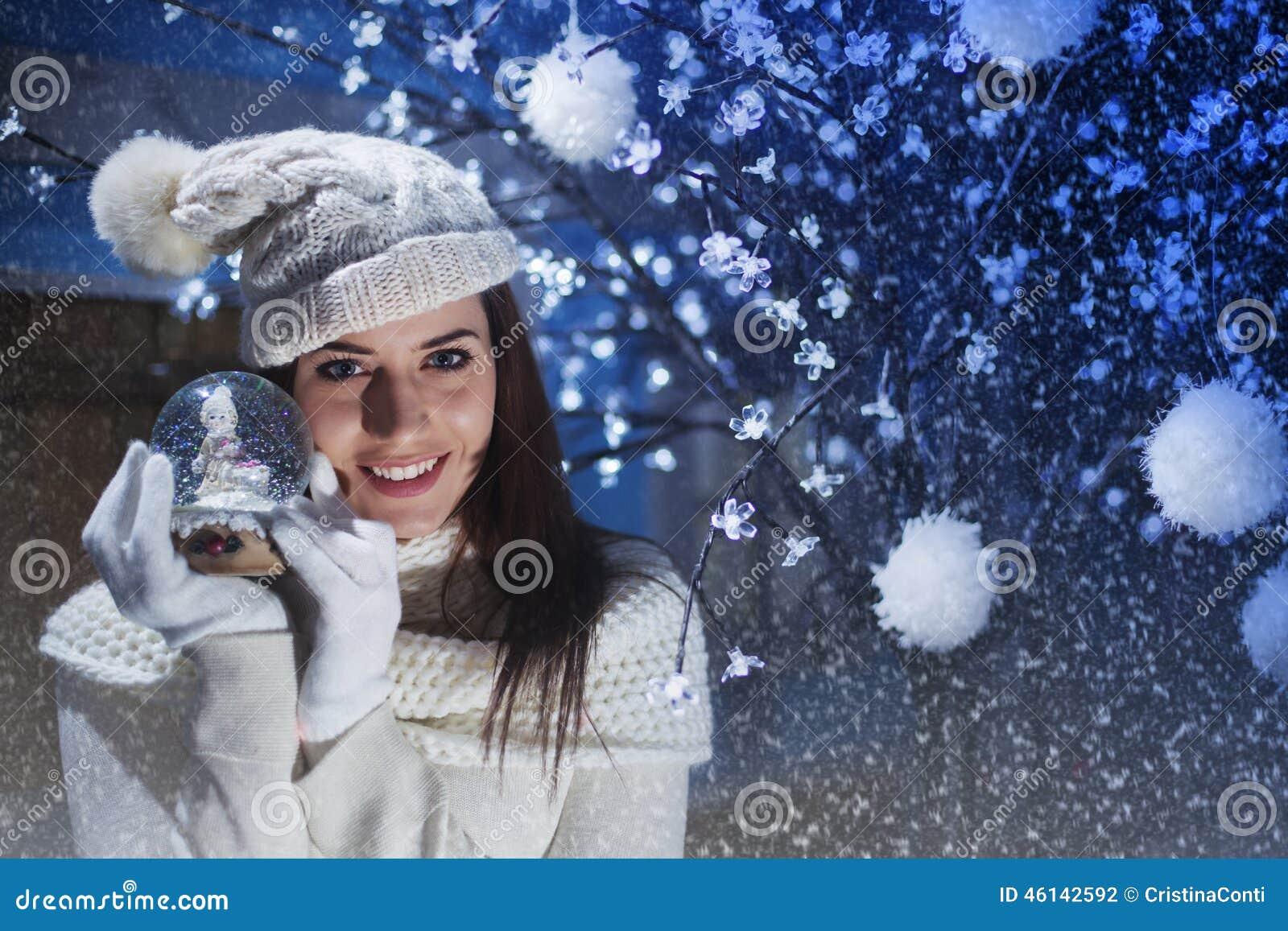 Las sonrisas hermosas de la mujer y muestran su Boule-de-neige